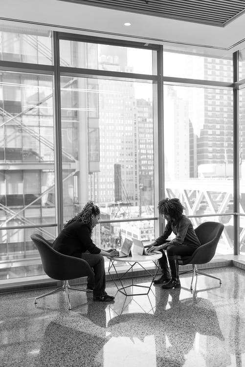 Grayscale Portrait of Two People Sitting on Chairs