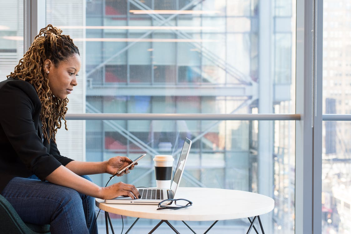 Woman Holding Smartphone Sitting in Front of Laptop on Table
