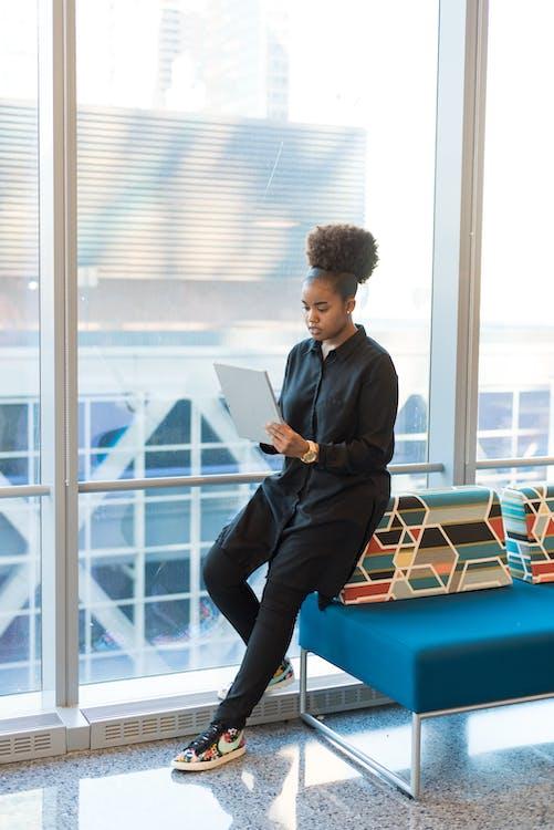 Woman in Black Jacket Standing Near Blue Sofa