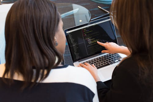 Two Women Looking at the Code at Laptop