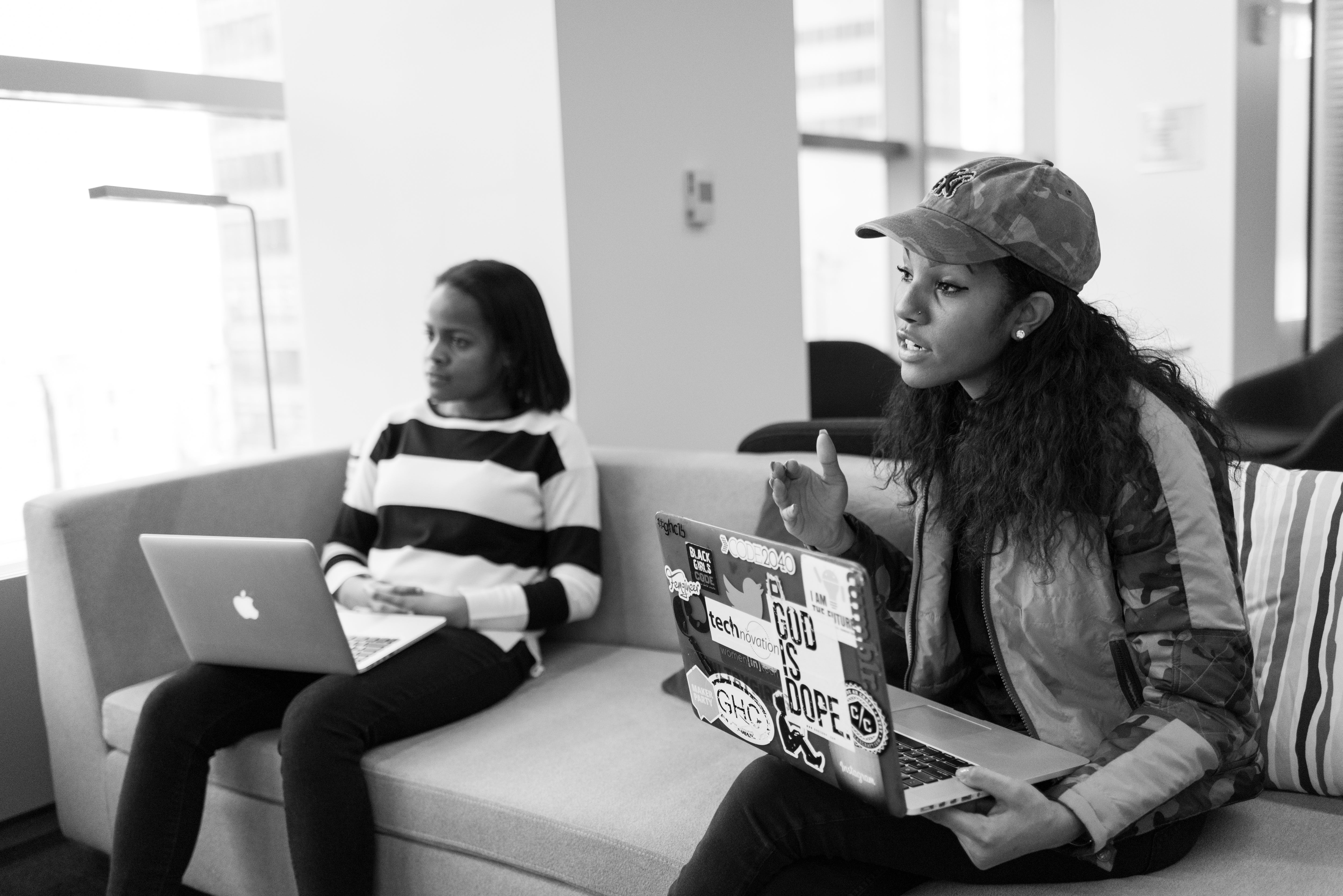 Two Women Sitting on Sofa Holding Laptop Computers
