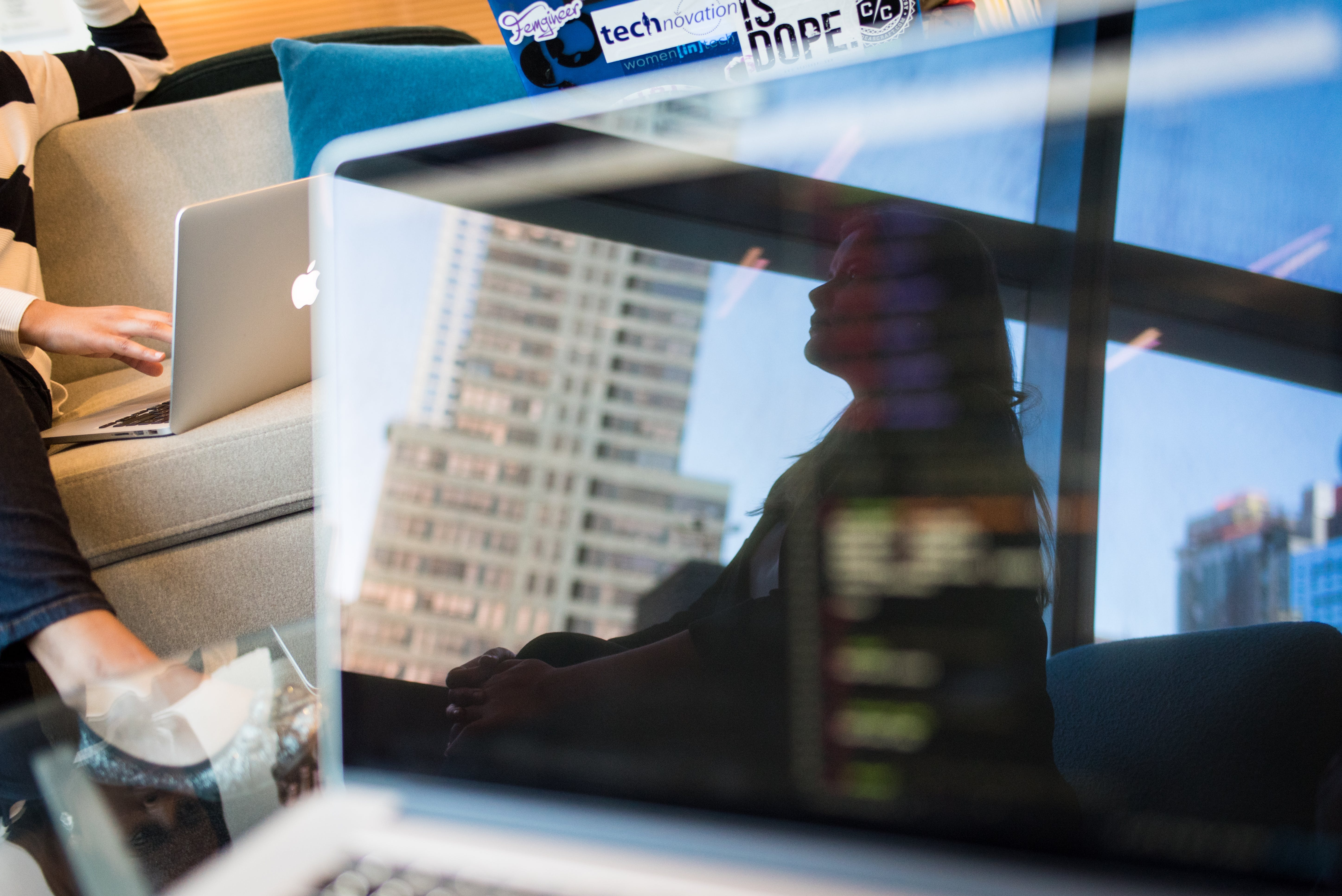 Photo of Gray Laptop Reflecting a Sitting Woman