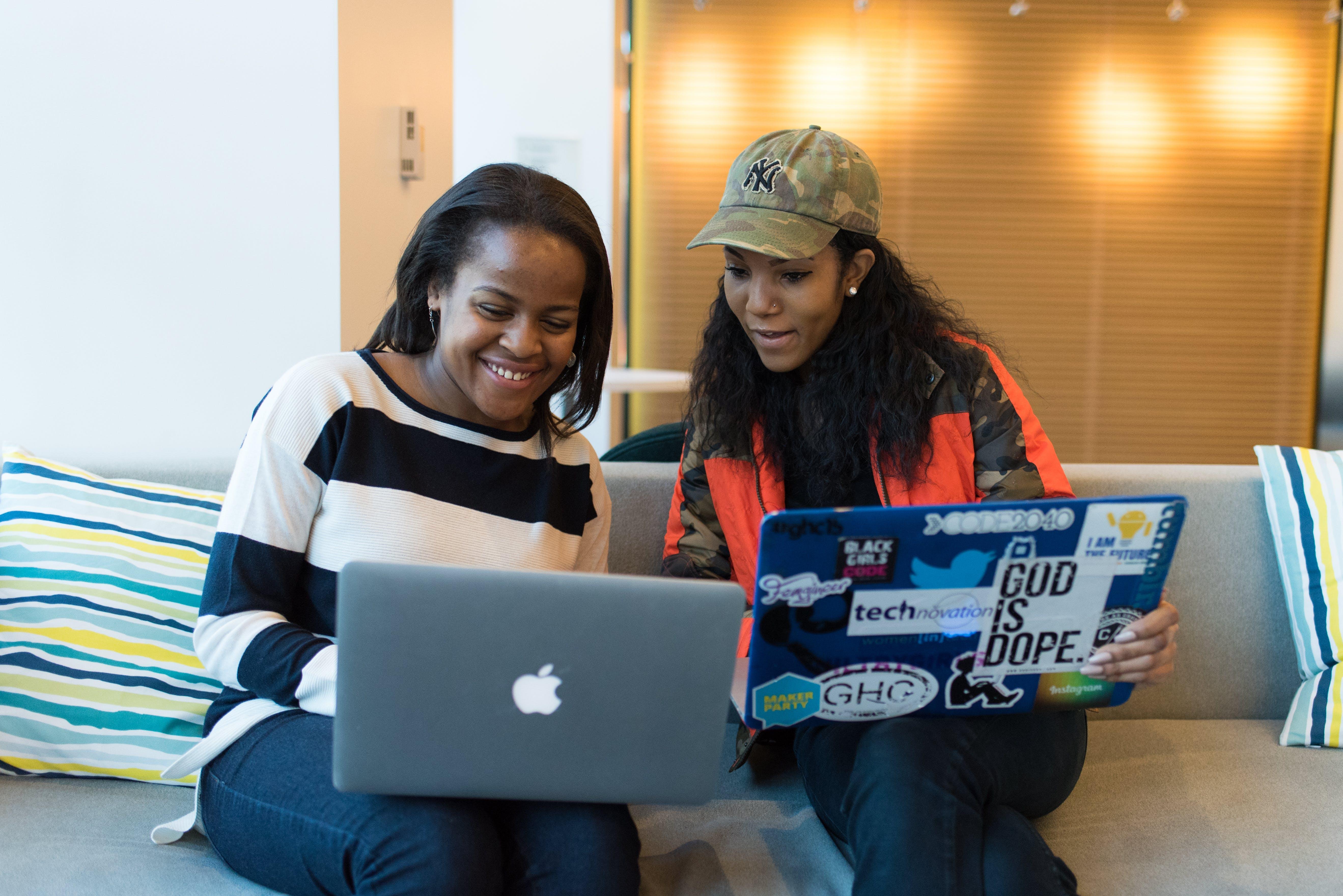 Two Women Holding Laptop