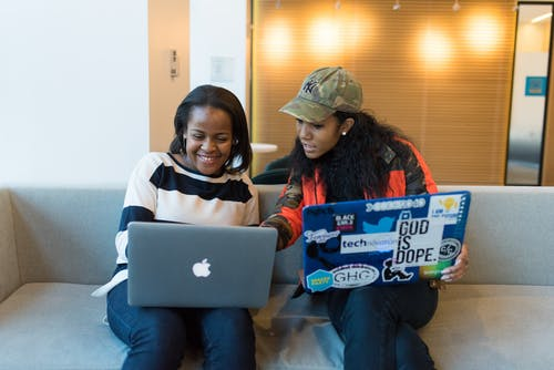 Two Woman Sitting On Sofa While Using Laptops