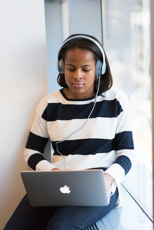 Woman Listening Through Headphones Using Macbook