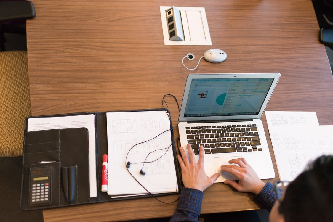 Person in Blue Dress Shirt Facing White Laptop on Brown Wooden Table