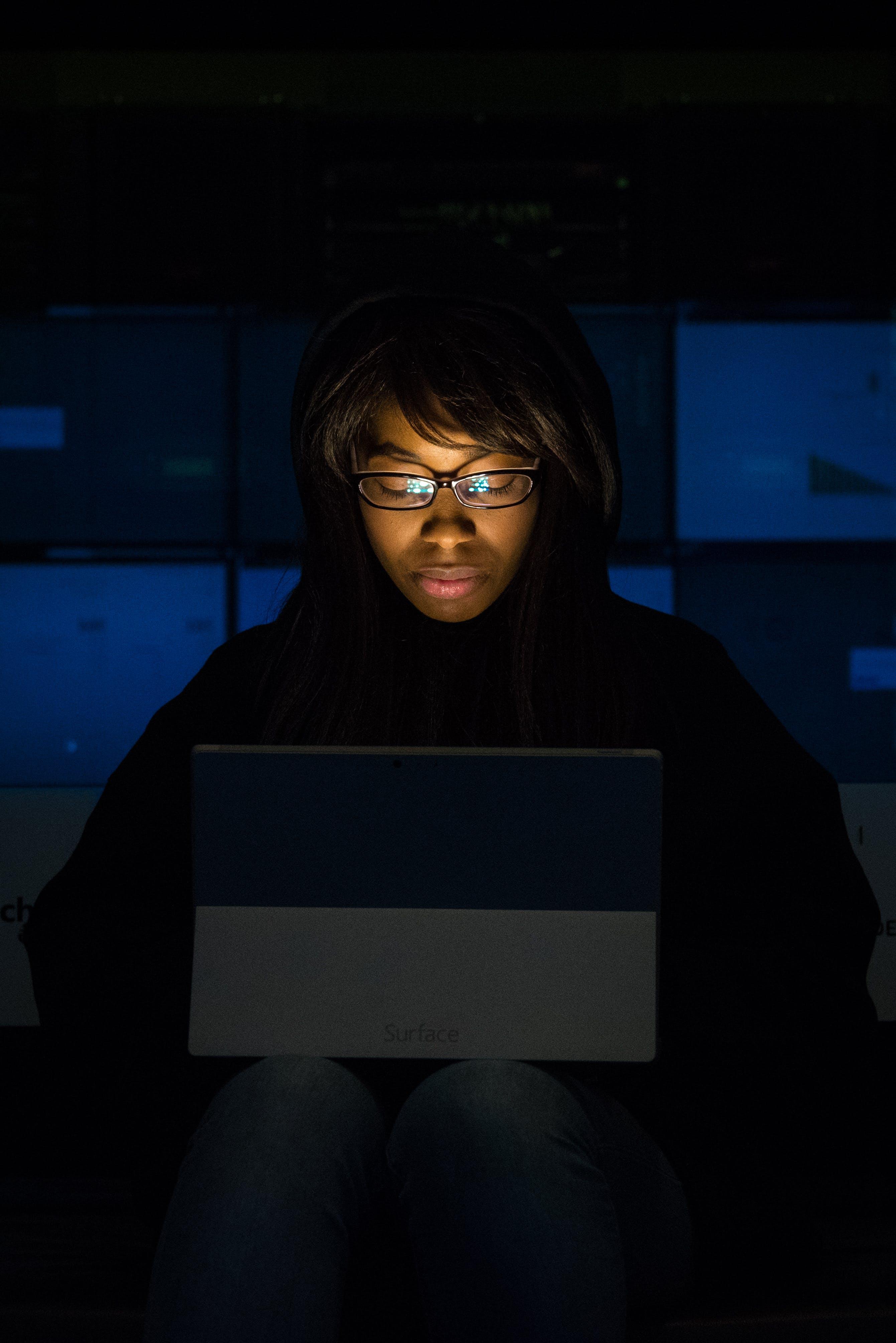 Woman Wearing Eyeglasses Looking at Tablet Computer in Dark Room