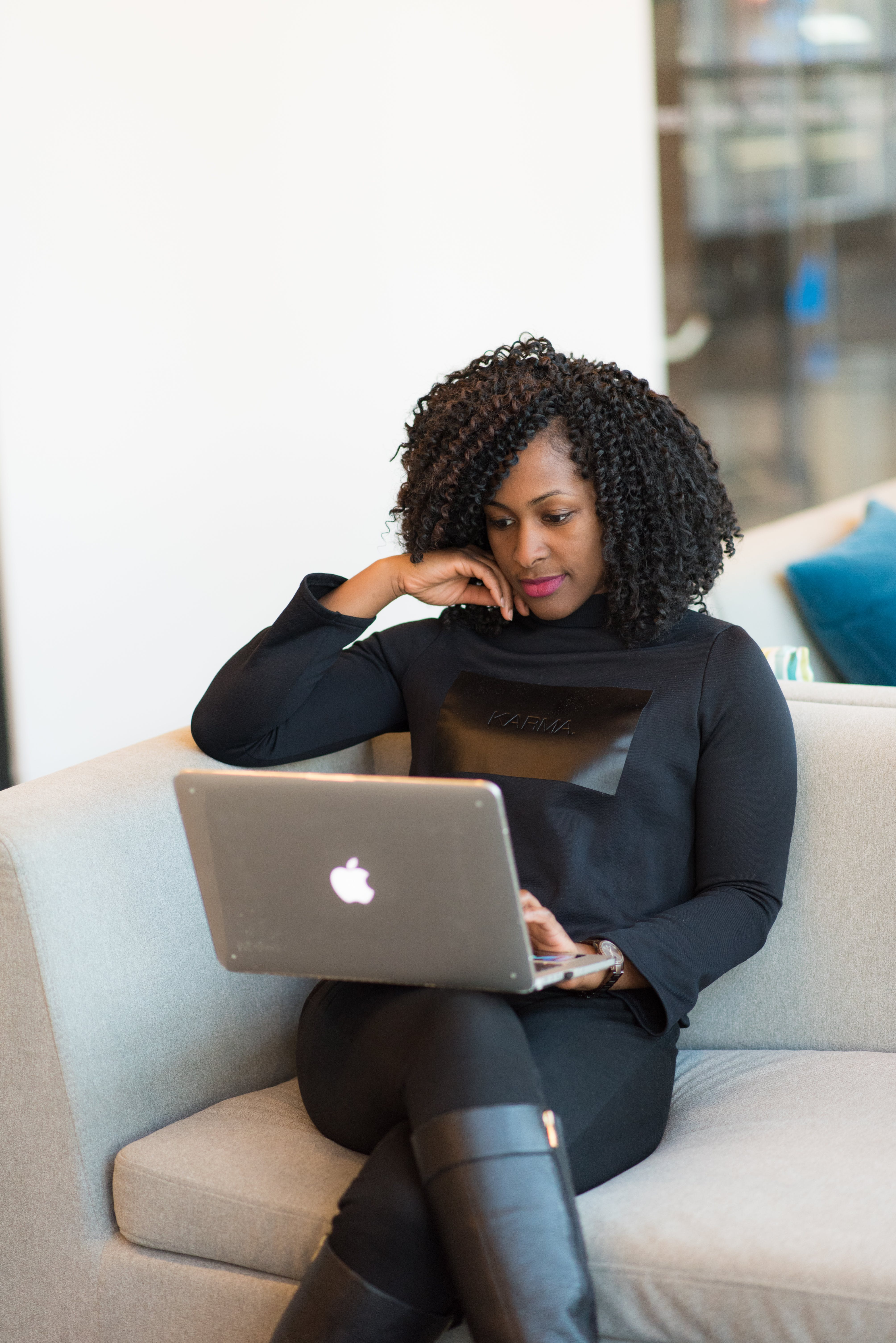 Woman in black outfit with MacBook sitting on a couch.