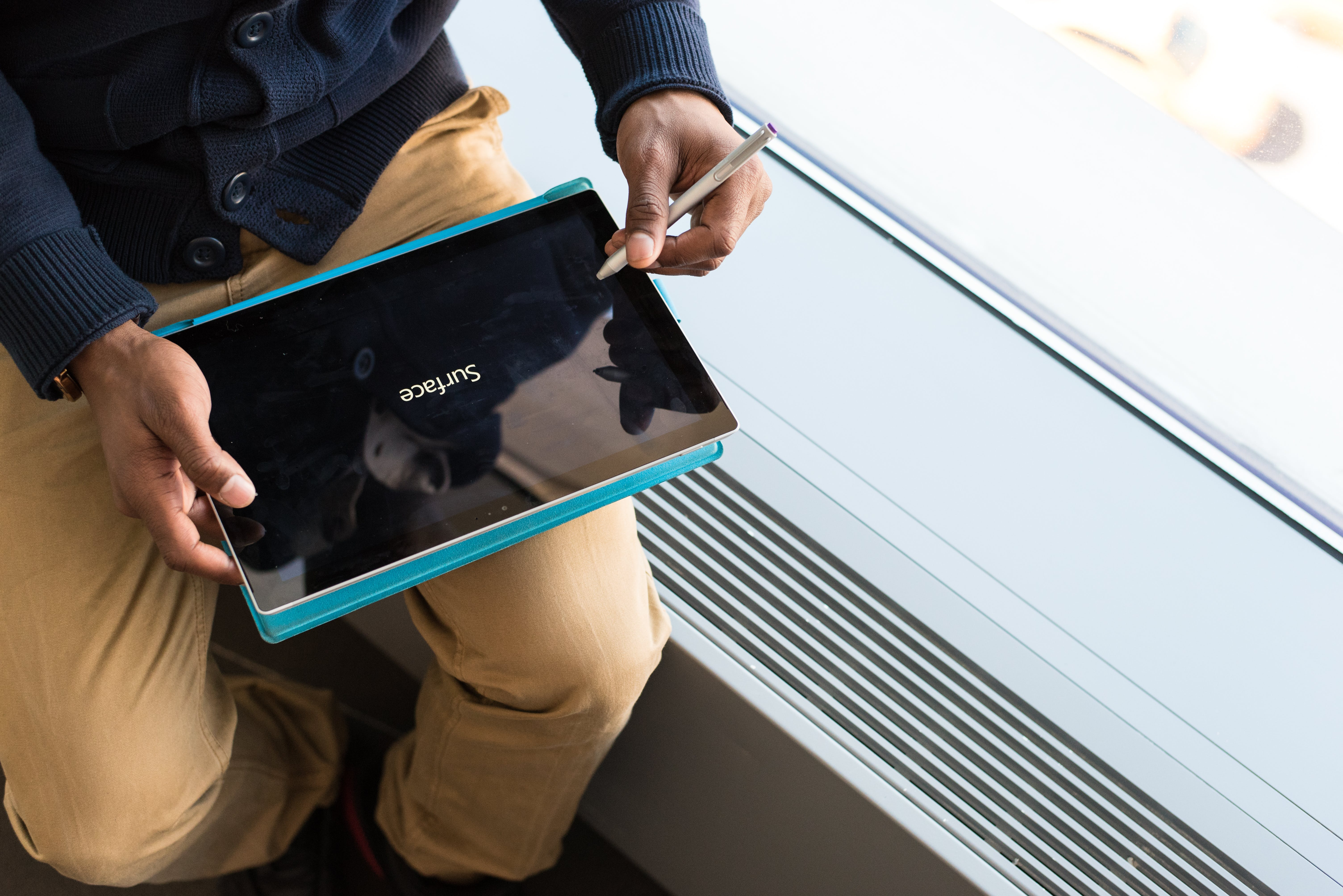 Person Wearing Brown Pants Holding Black Tablet Computer