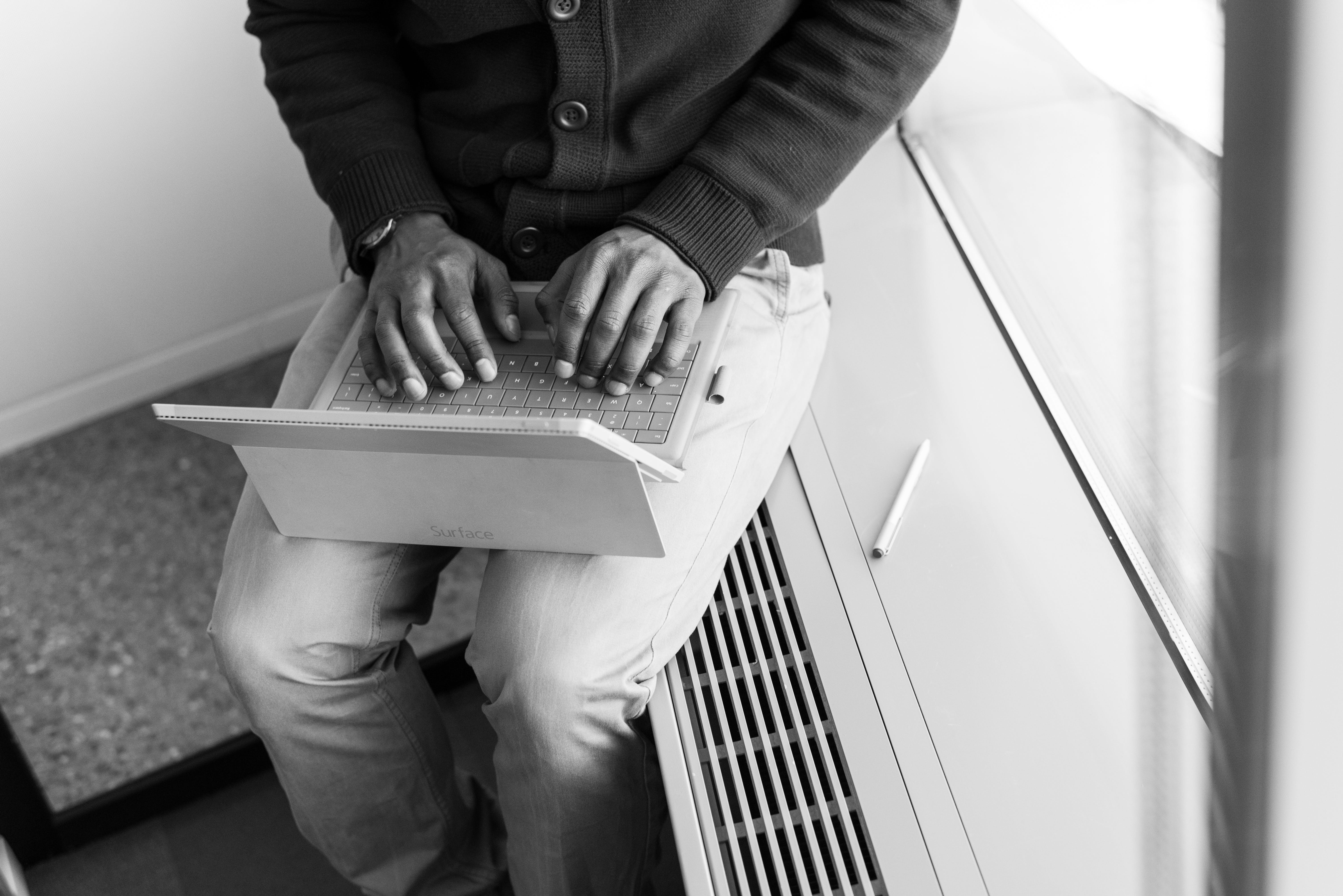 Greyscale Photo of Man Using Laptop Computer