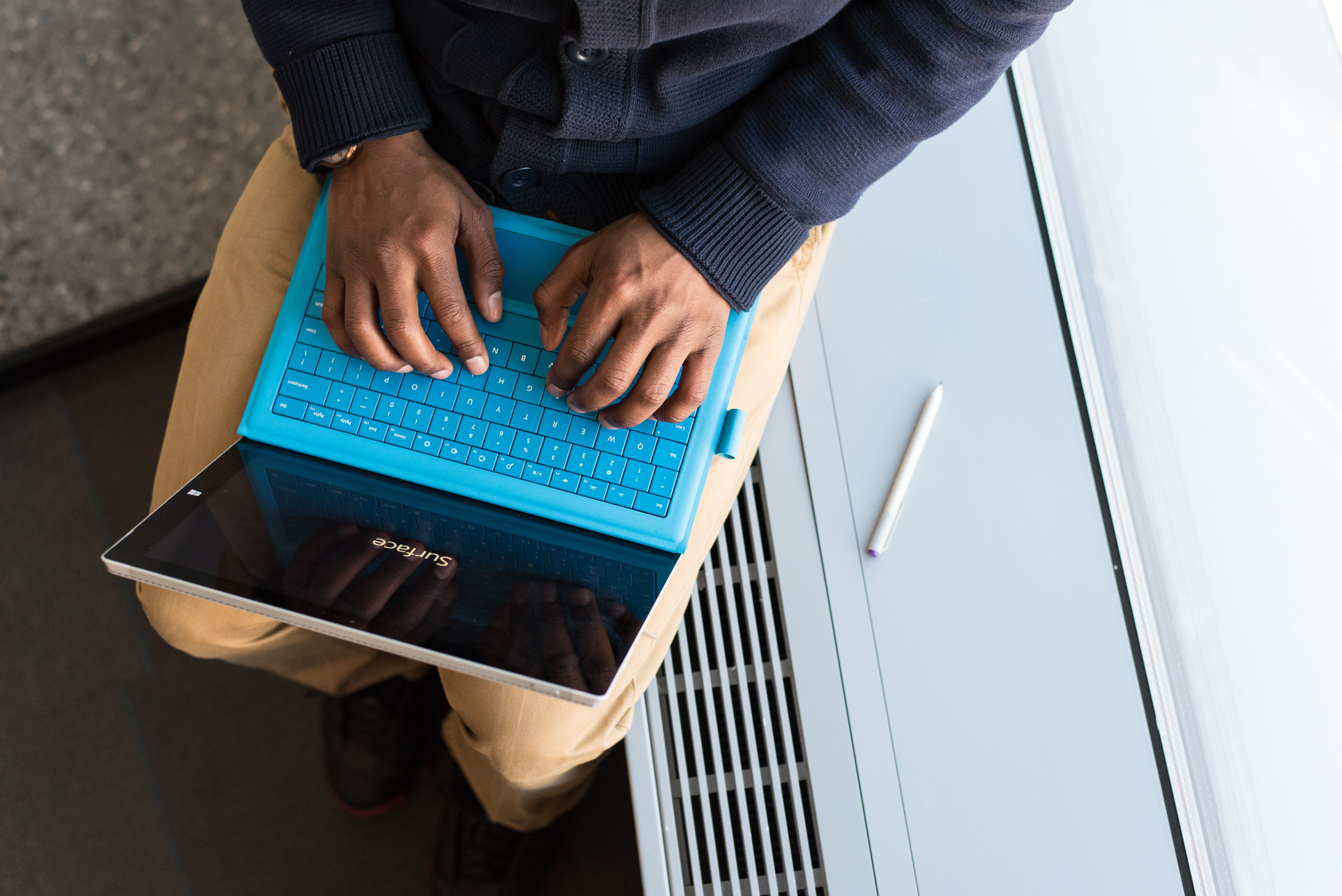 Person Typing on Blue Laptop Computer