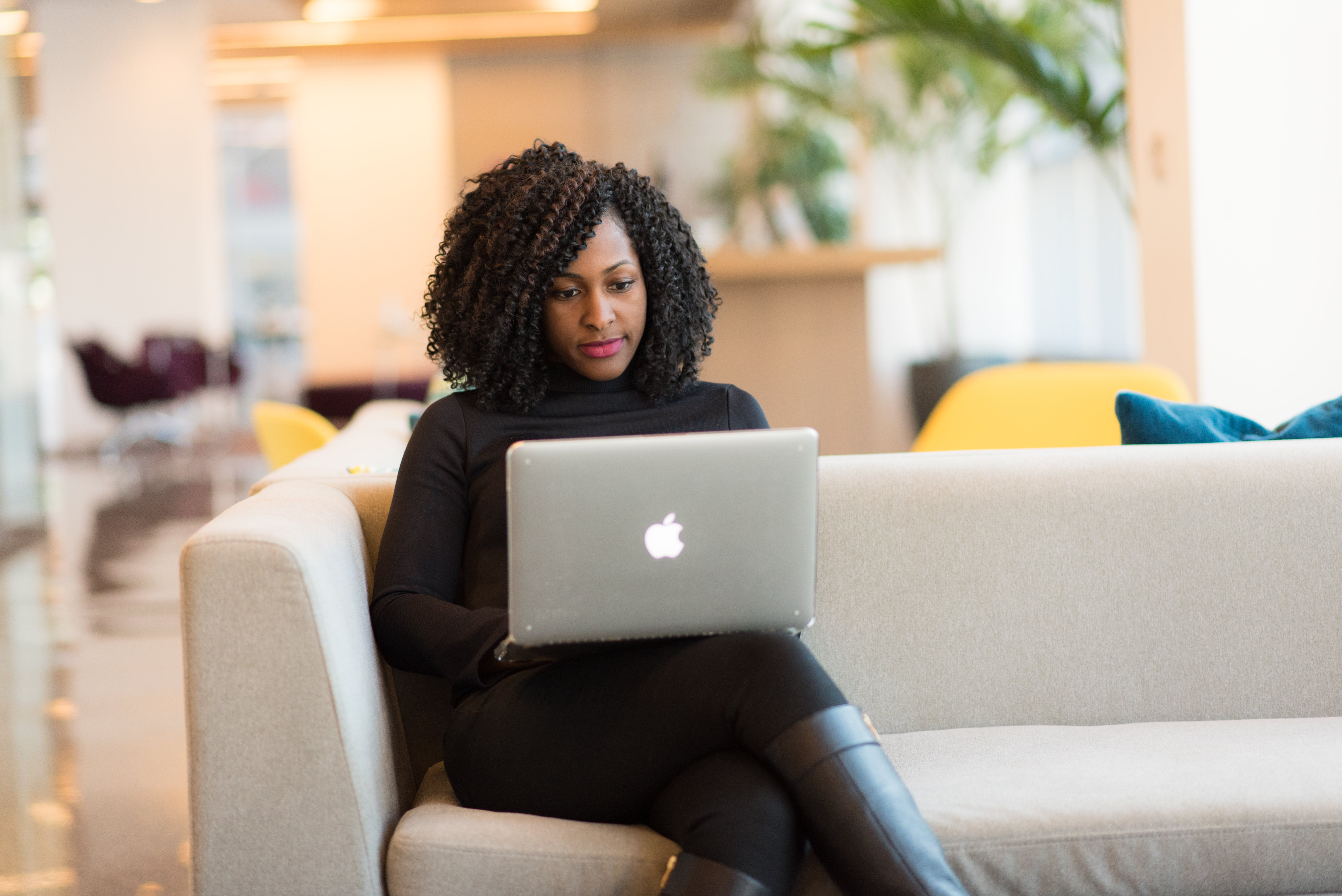 Woman Using Macbook Sitting on White Couch