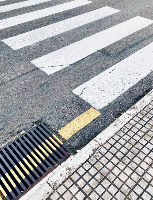 Crosswalk marked on asphalt road near sewer grid in city