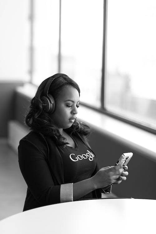 Gri Tonlamalı Kablosuz Kulak üstü Kulaklık Takan Akıllı Telefon Tutan Kadın Fotoğrafı