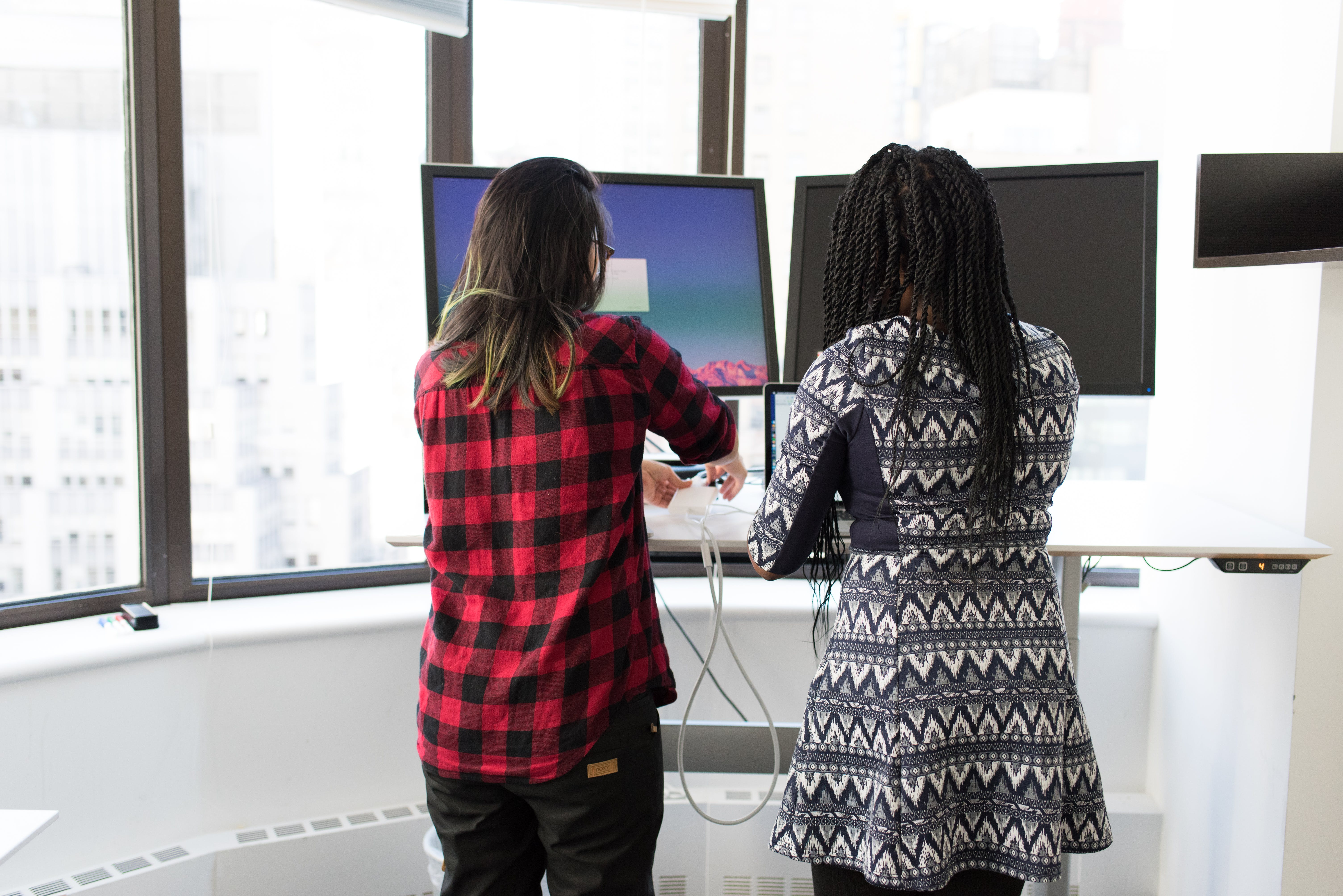 Two Women Standing in Front of Television