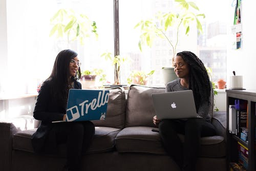 Two Women Sitting on Gray Fabric 2-seat Sofa Staring at Each Other While Carrying Laptop Computers