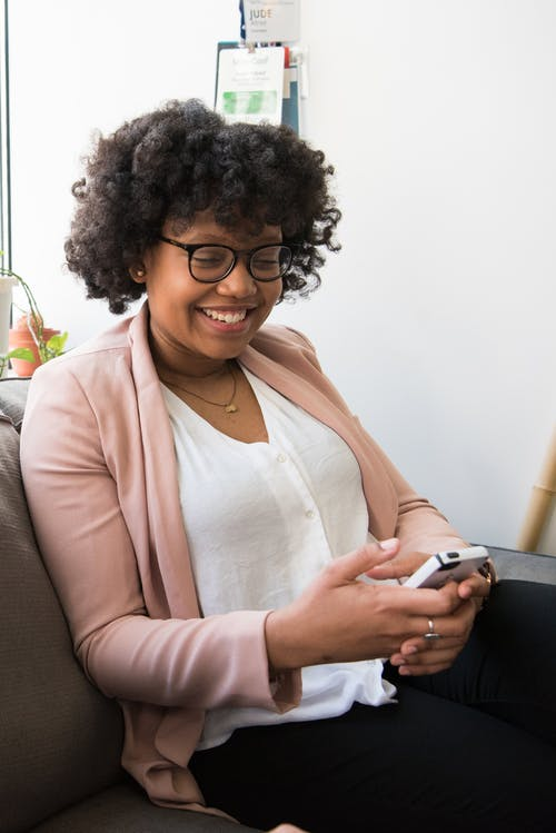 Smiling Woman Wearing White Top and Pink Cardigan Holding Iphone Sitting on Couch