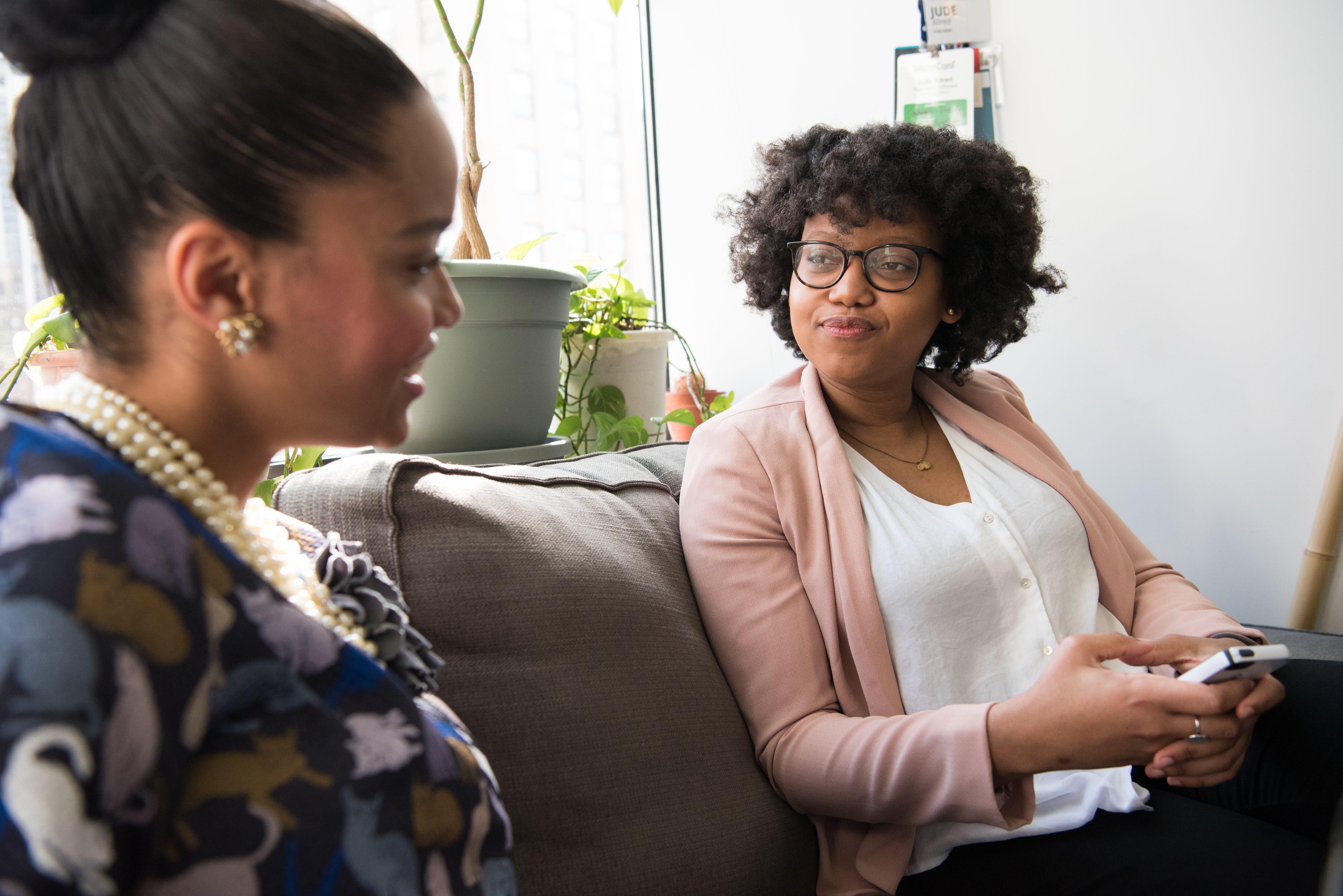 Two Women on Sofa Chatting