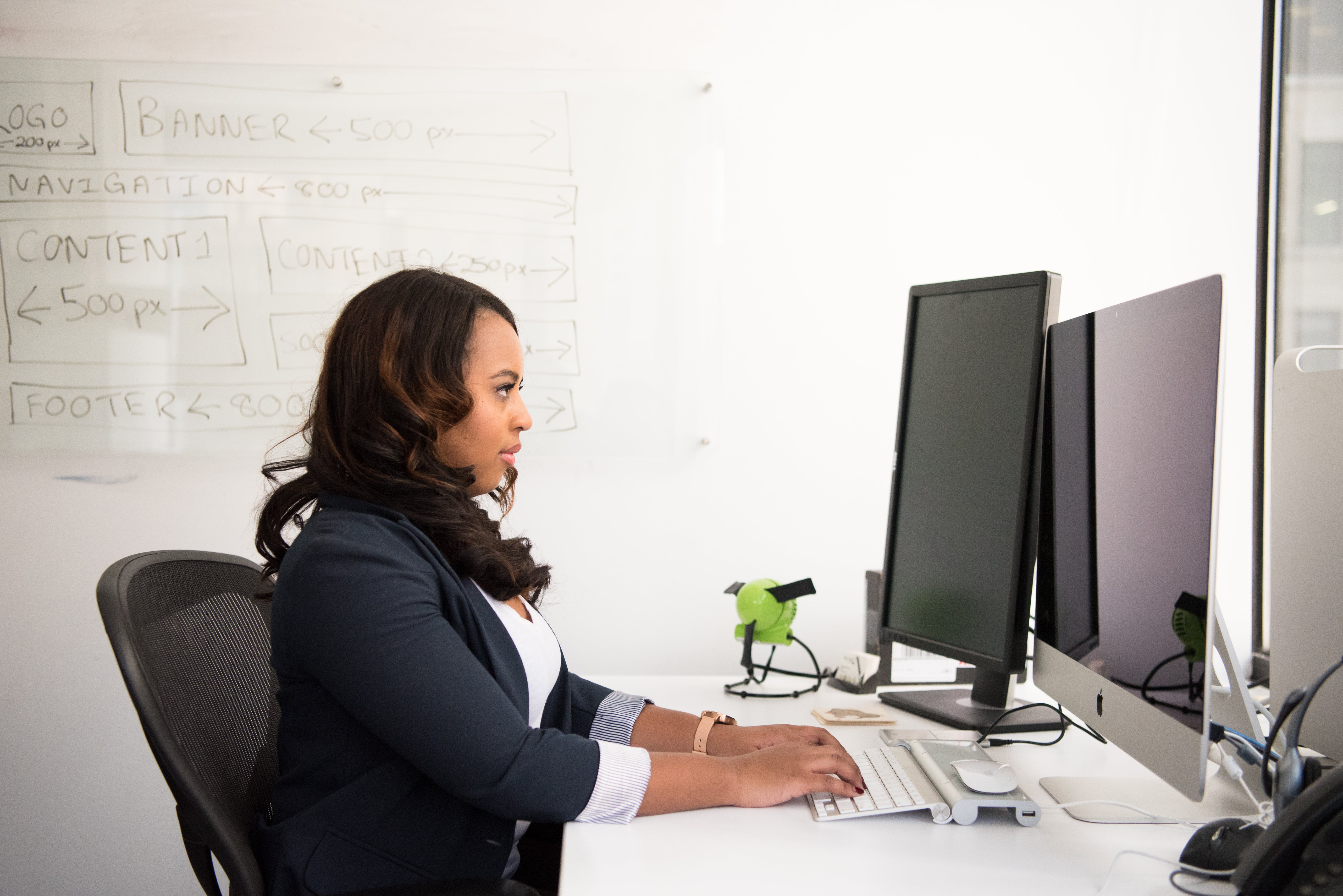 Woman Wearing Black Coat Sitting on Chair Using Computer
