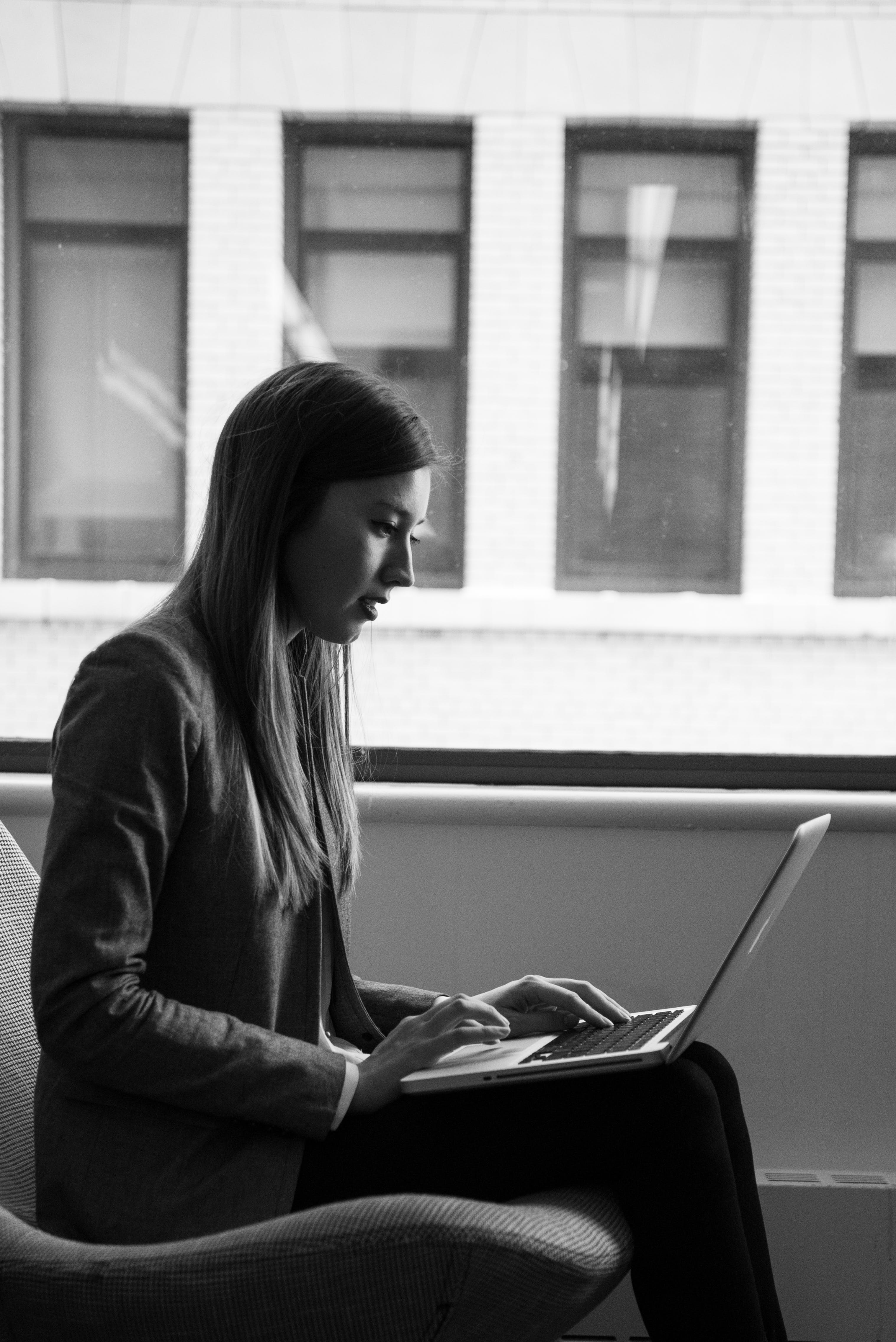 Grayscale Photography of Woman in Suit Coat Using Laptop Computer