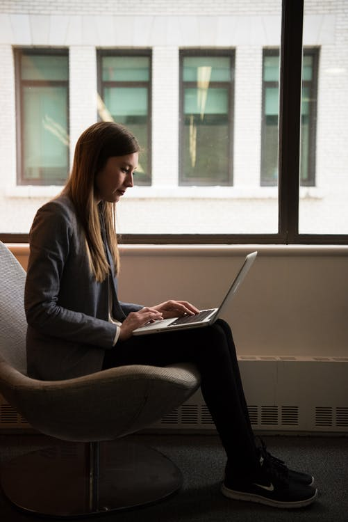 Woman Sits and Use Laptop Computer Near Window