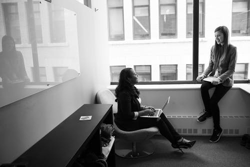 Grayscale Photo of Woman Talking to Her Colleague