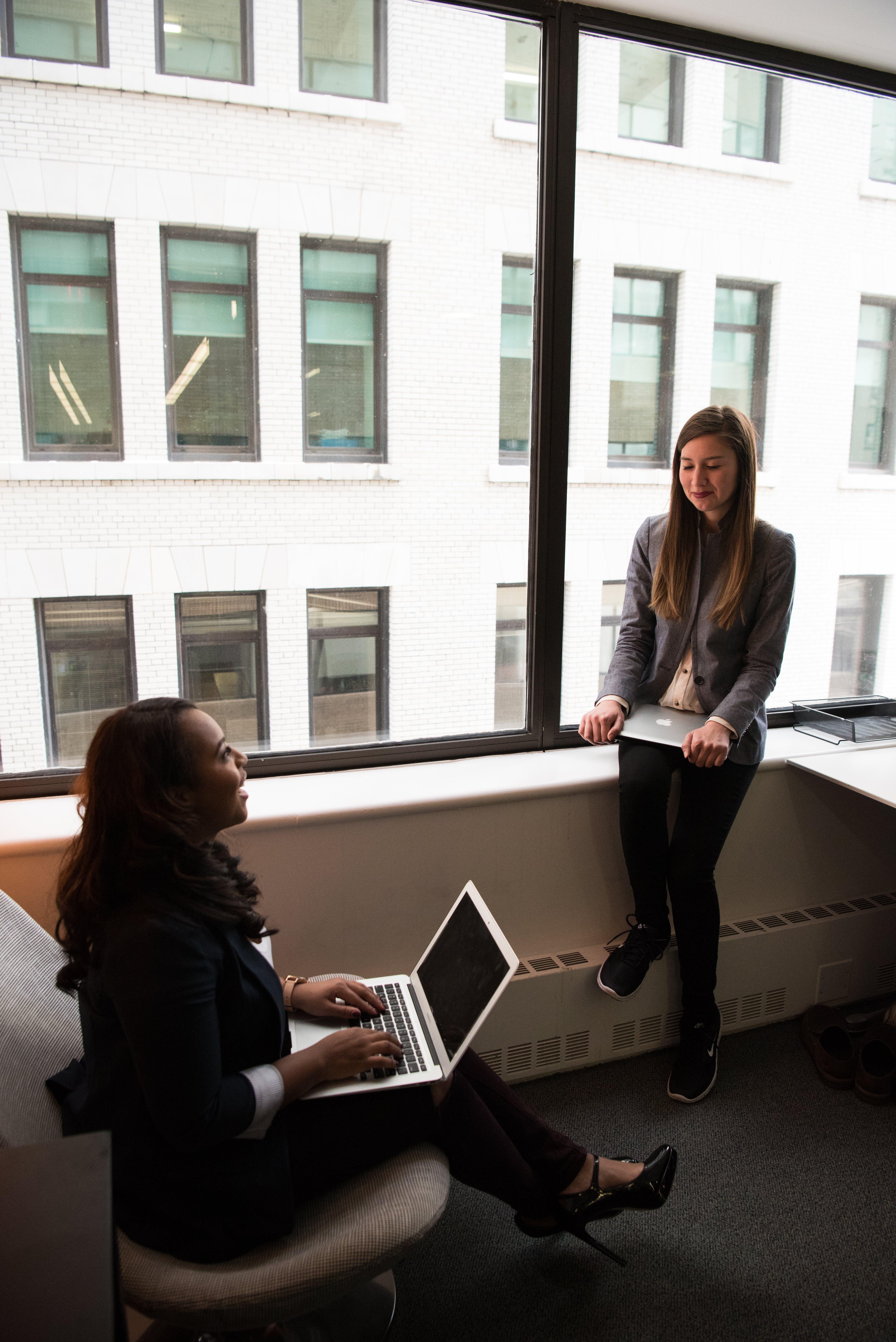 Two Women Talking White Holding Laptop Computers