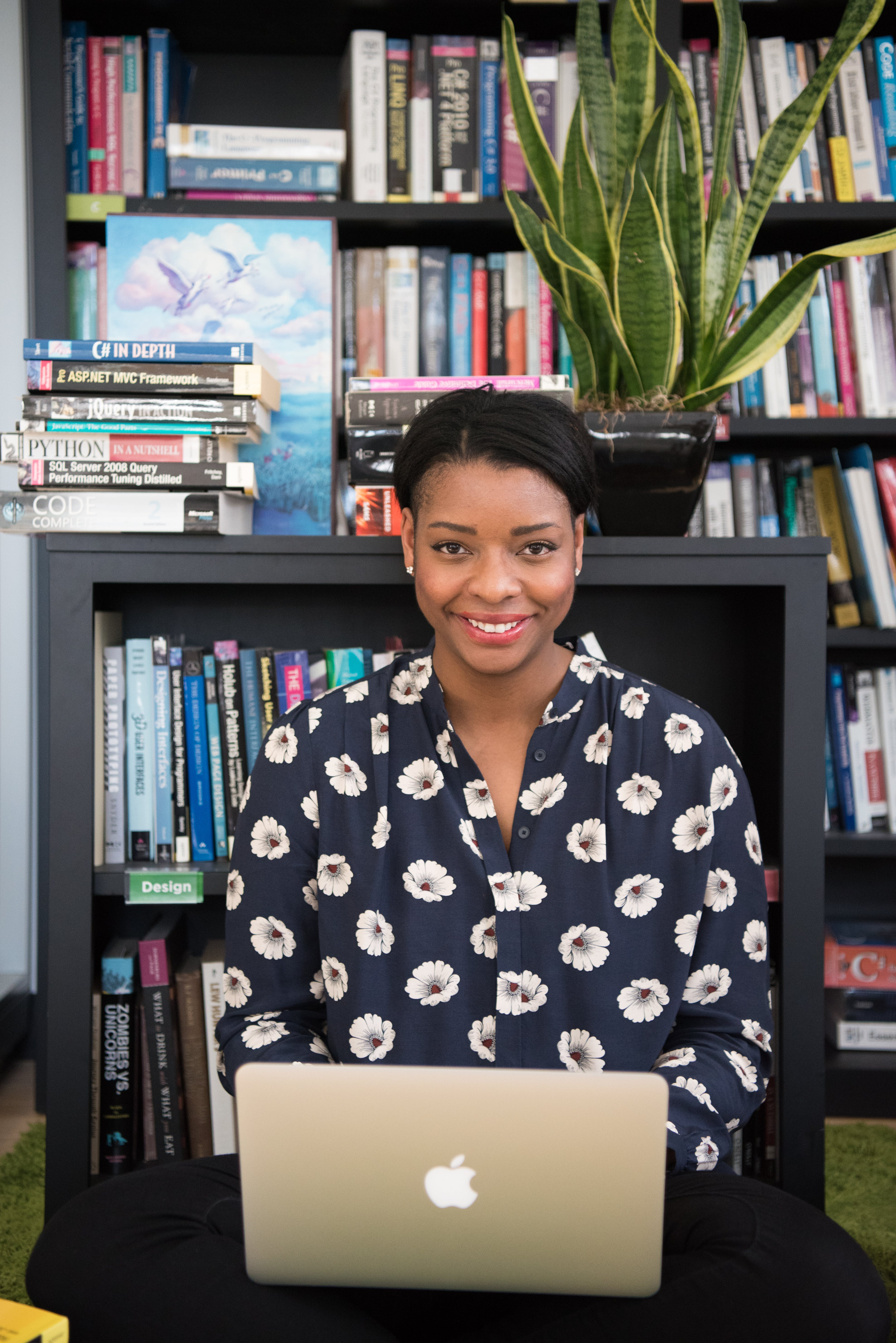 Woman in Black Floral Long-sleeved Top Near Book Shelves