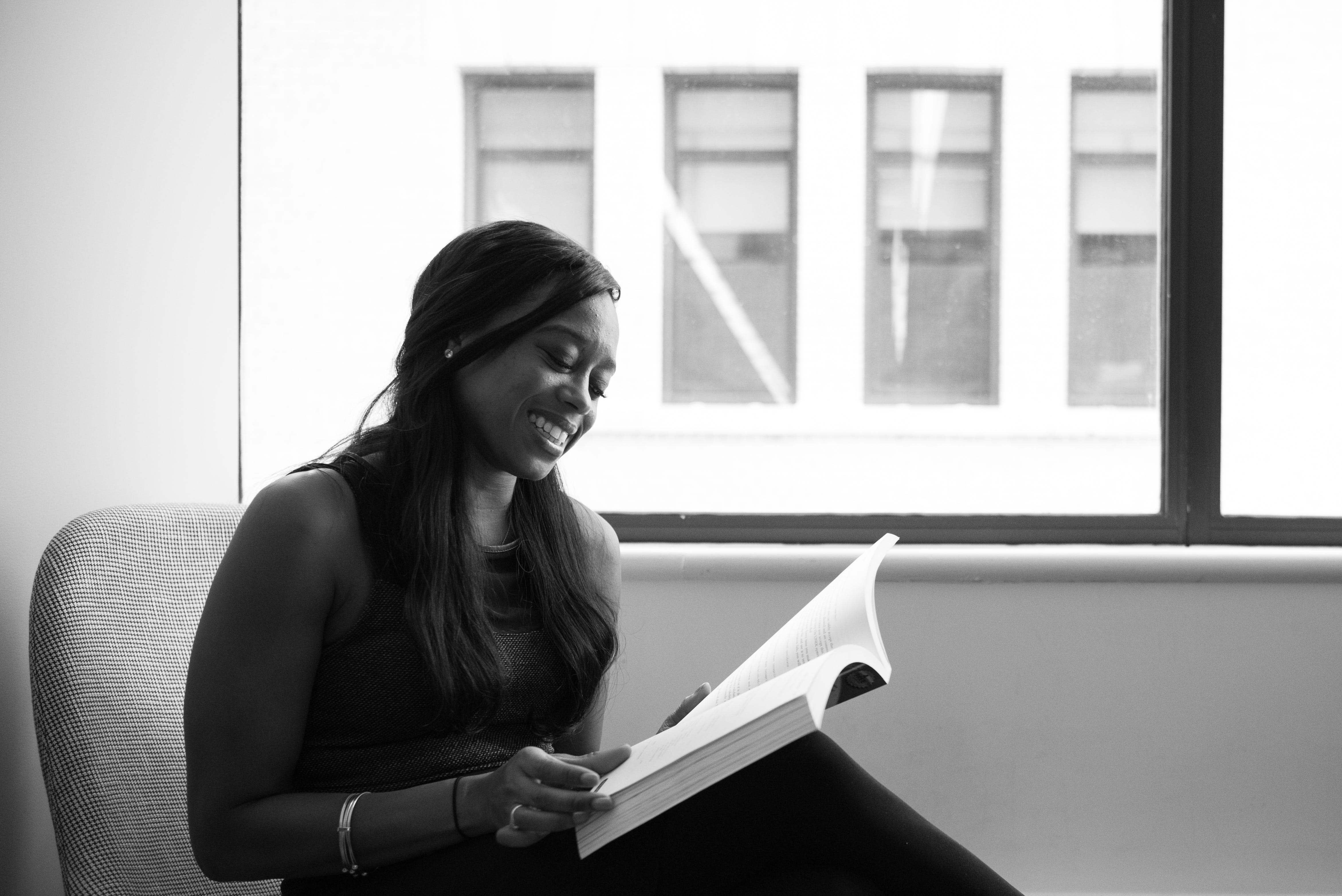 Grayscale Photo of Smiling Woman Reading Book