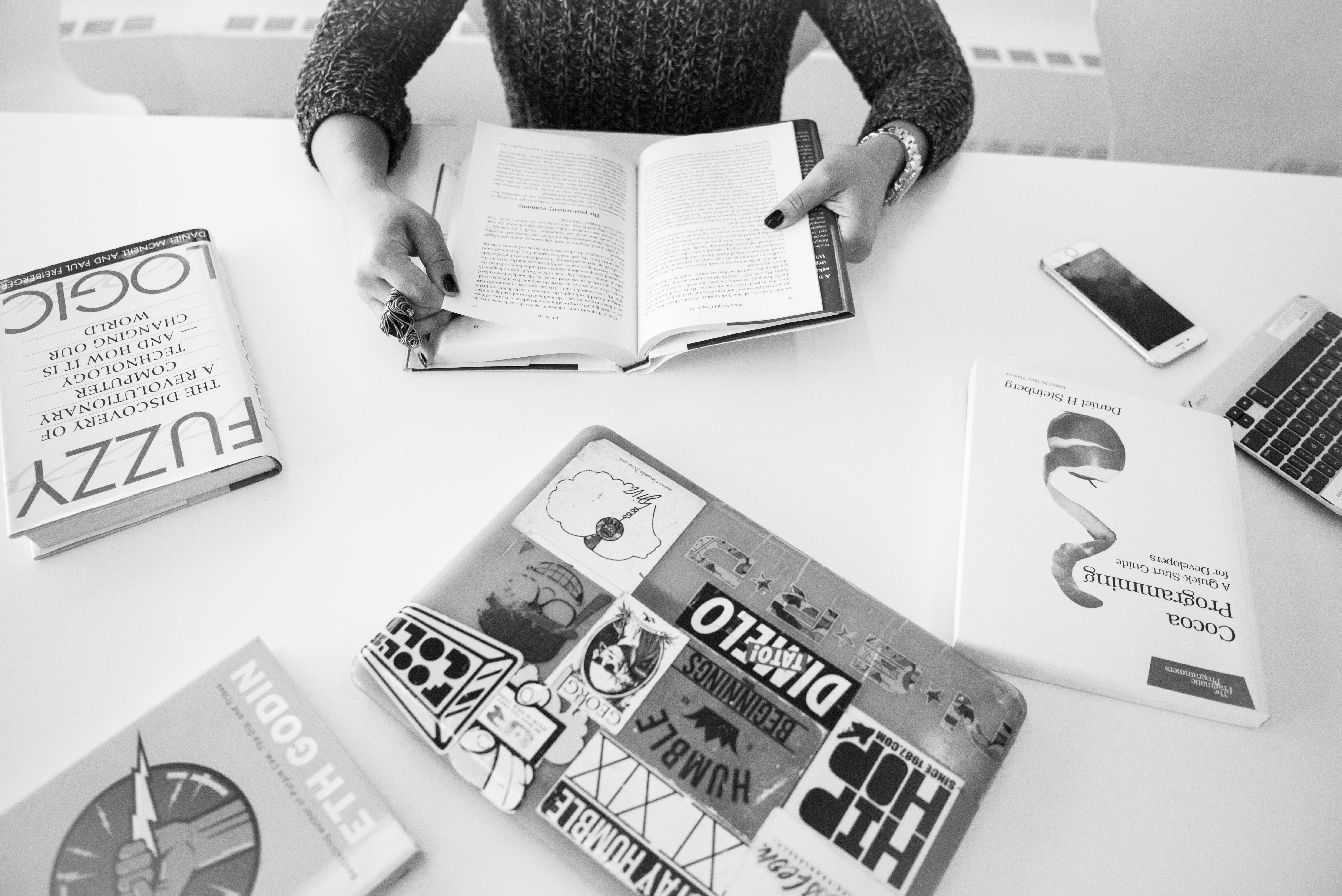Grayscale Photo of Person Sitting Near Table With Books