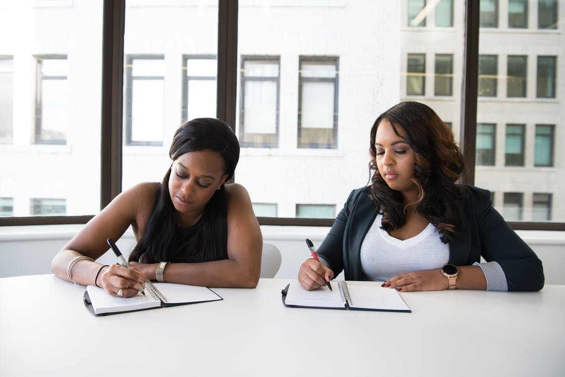 Two Women Holding Pen Writing Down Notes