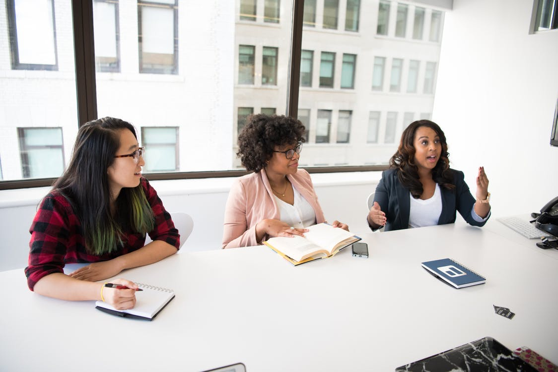 Three Women in Front of Desk