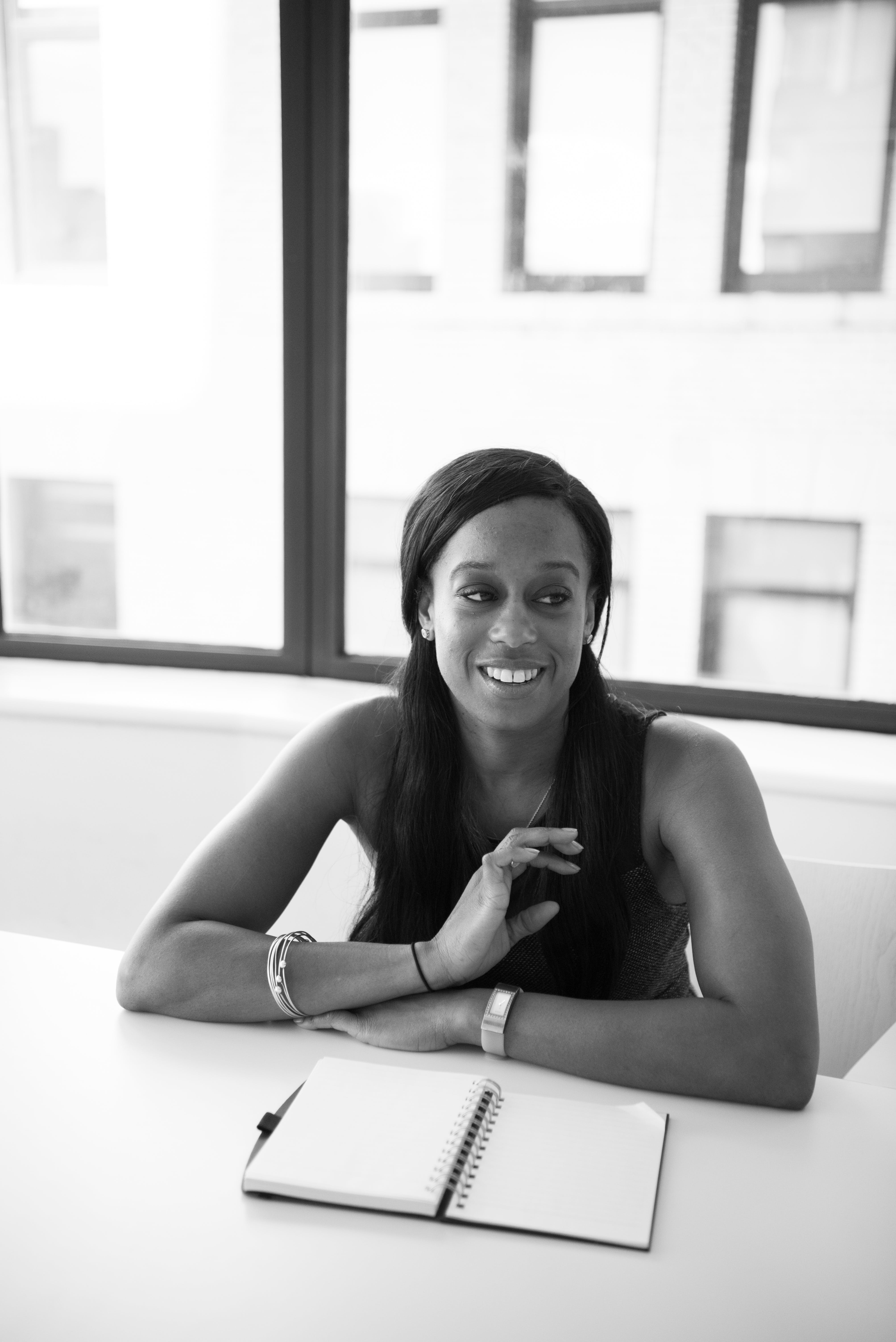 Grayscale Photography of Woman in Sleeveless Top Sits Near Table
