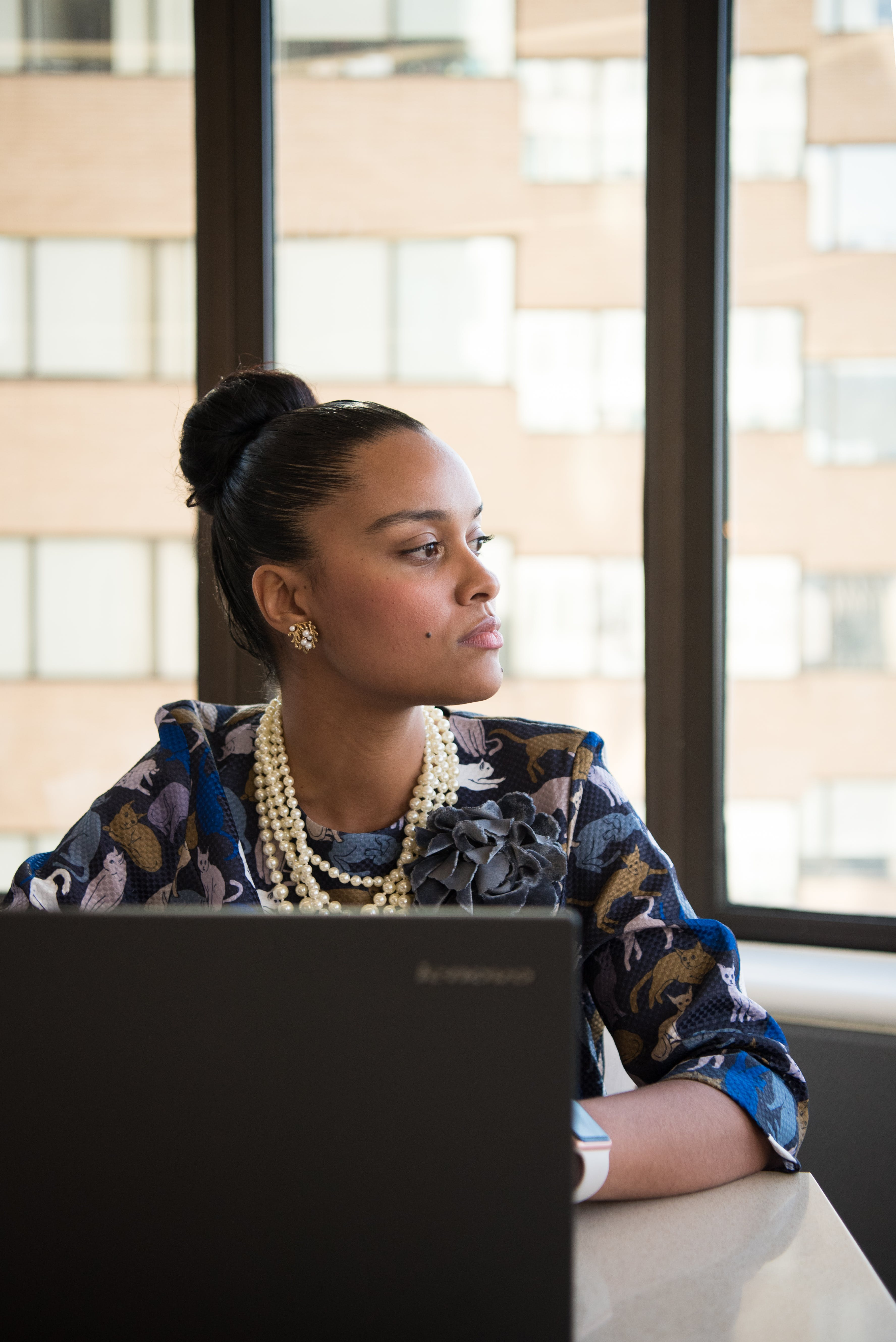 Woman Wearing Blue and Brown Floral Elbow-sleeved Dress Facing Black Lenovo Laptop Near Glass Window