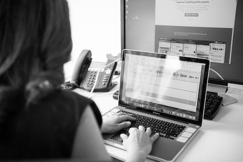 Grayscale Photo of Woman Using Macbook Pro