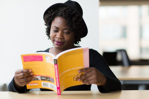 Woman in Black Long-sleeved Shirt Reading a Yellow Covered Book