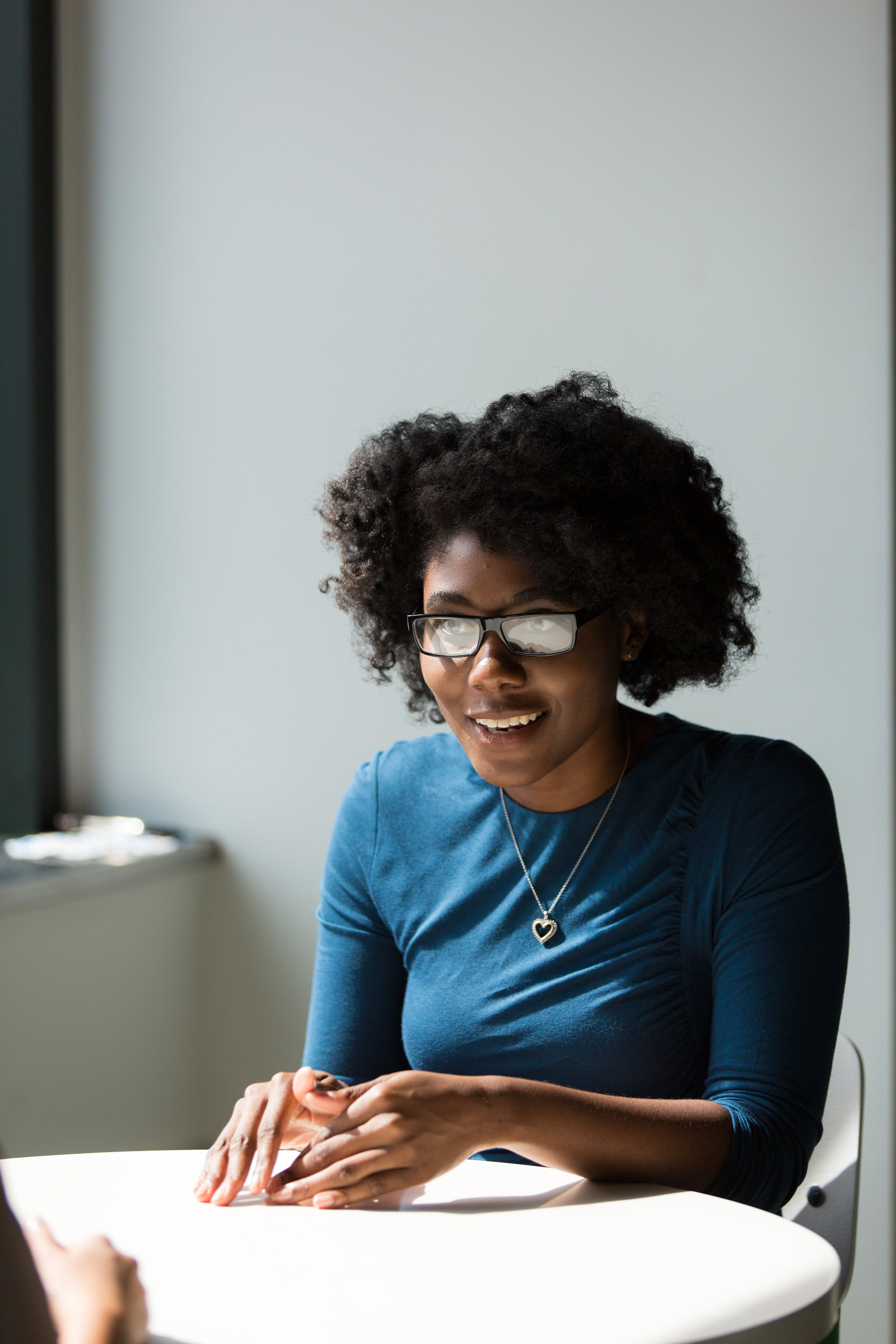 Woman Wearing Black Framed Eyeglasses and Blue Crew-neck Elbow-sleeved Top