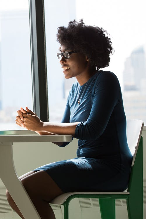 Woman Wearing Eyeglasses Sitting Beside Table and Window