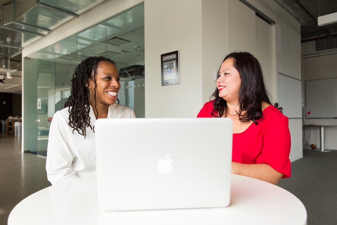 Two Women in Front of Silver Macbook