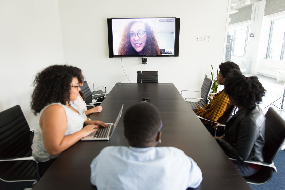 Diverse coworkers having online conference in modern office