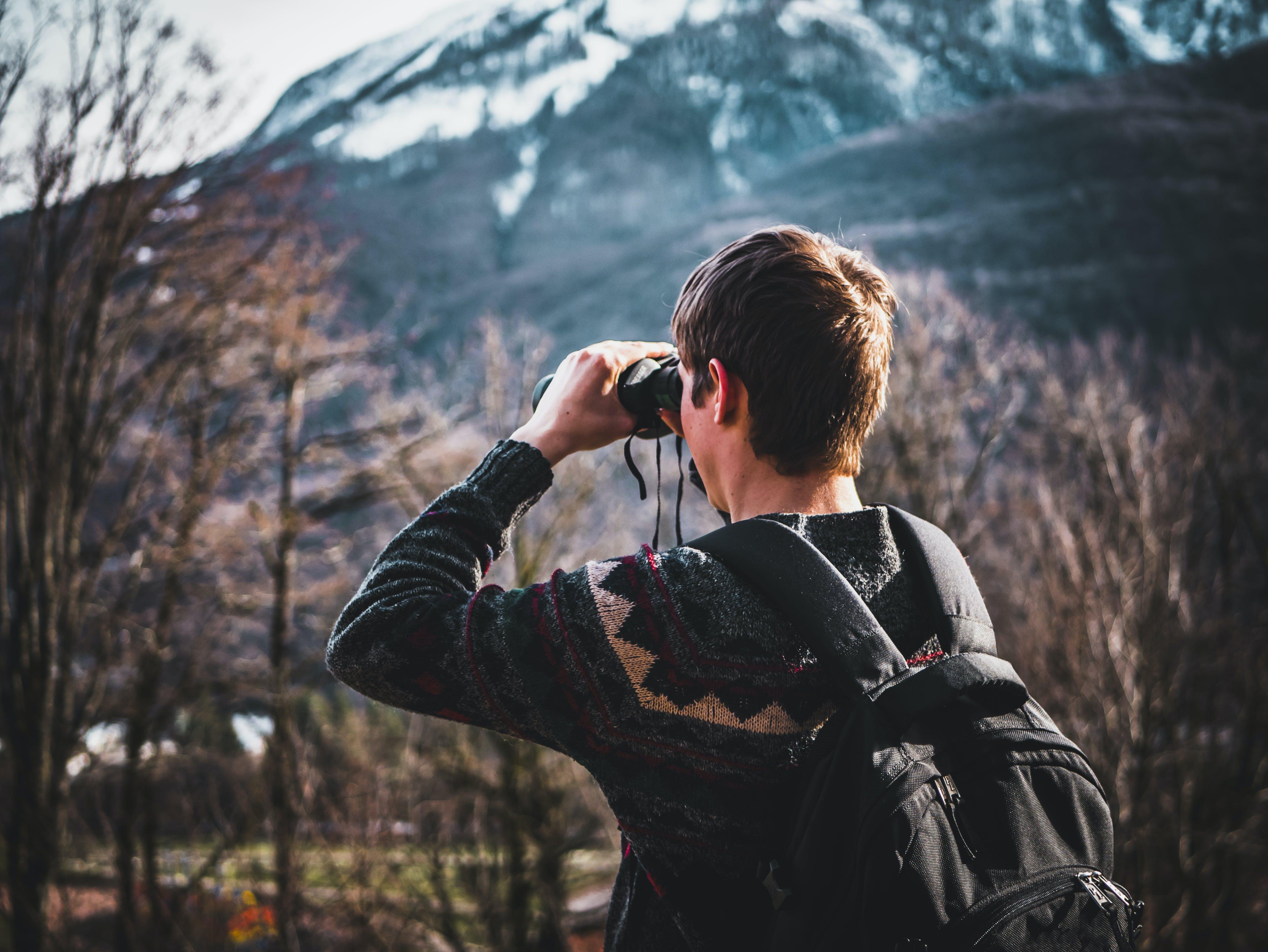 Man Using Black Binoculars Near Forest Trees at Daytime