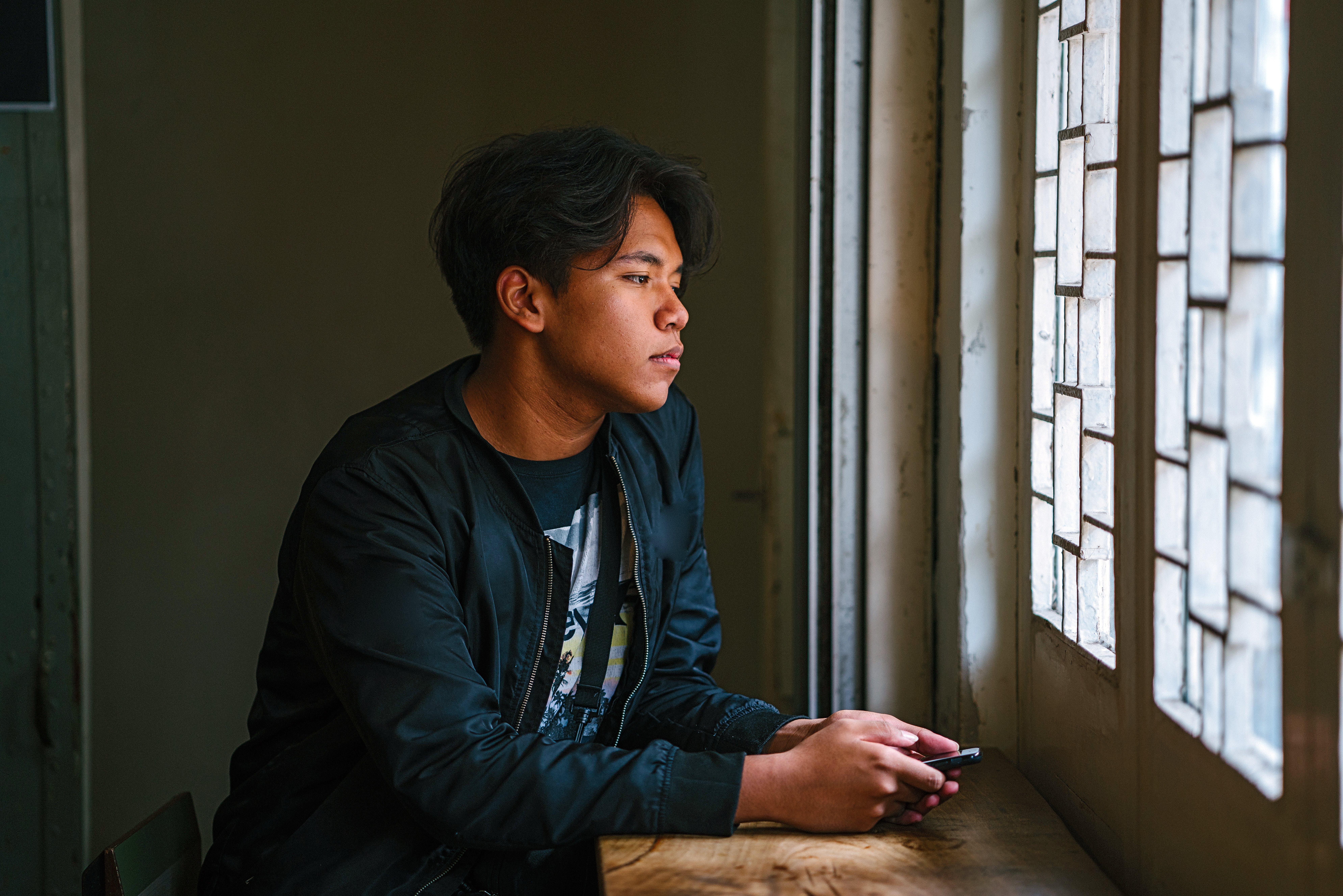 Man Beside Window Wearing Black Jacket
