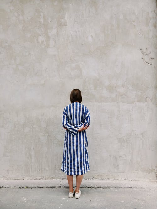 Woman Wearing Blue and White Striped Shirt Dress Facing Gray Wall
