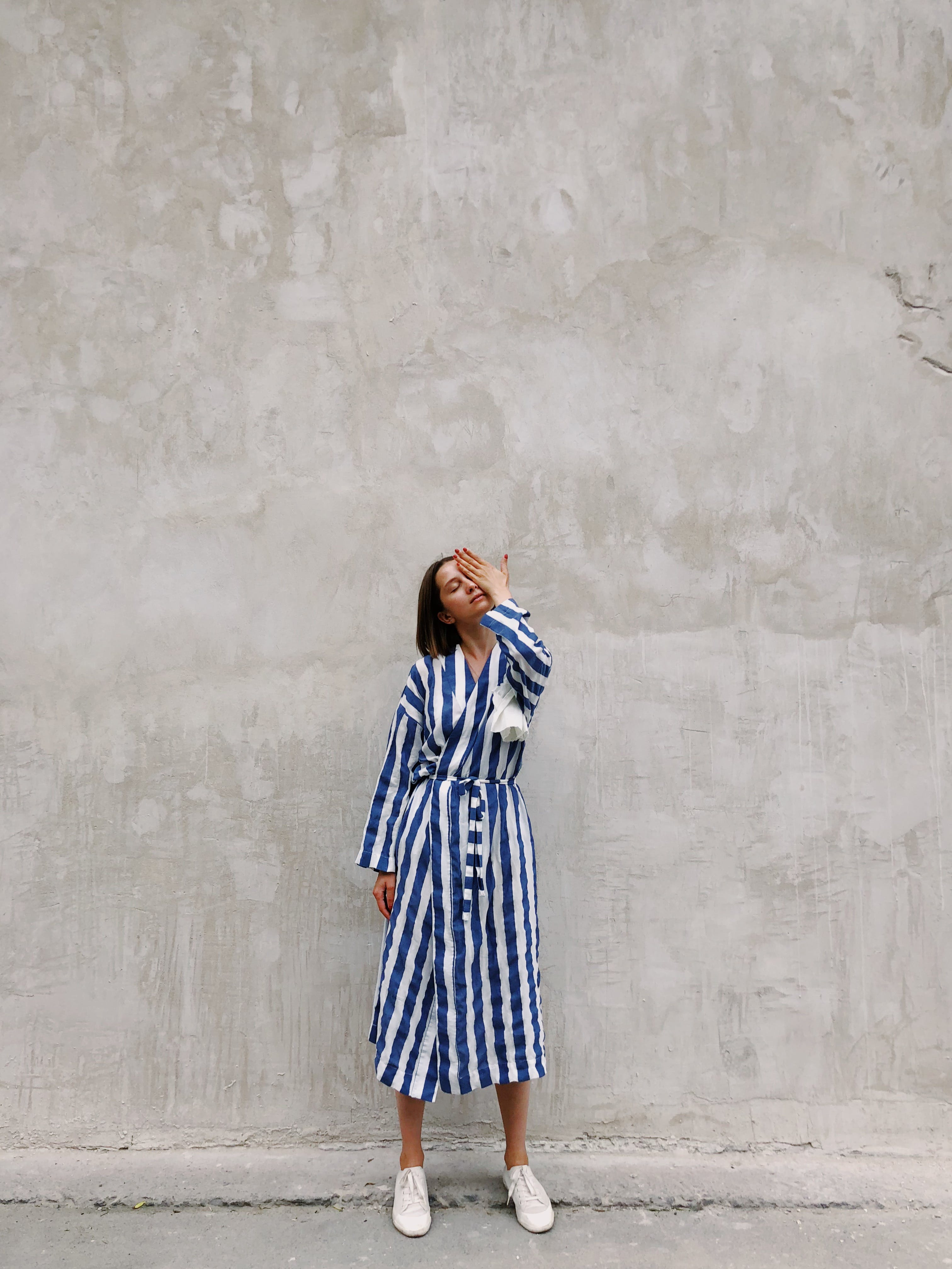 Woman in Blue and White Striped Dress Covering Her Left Eye