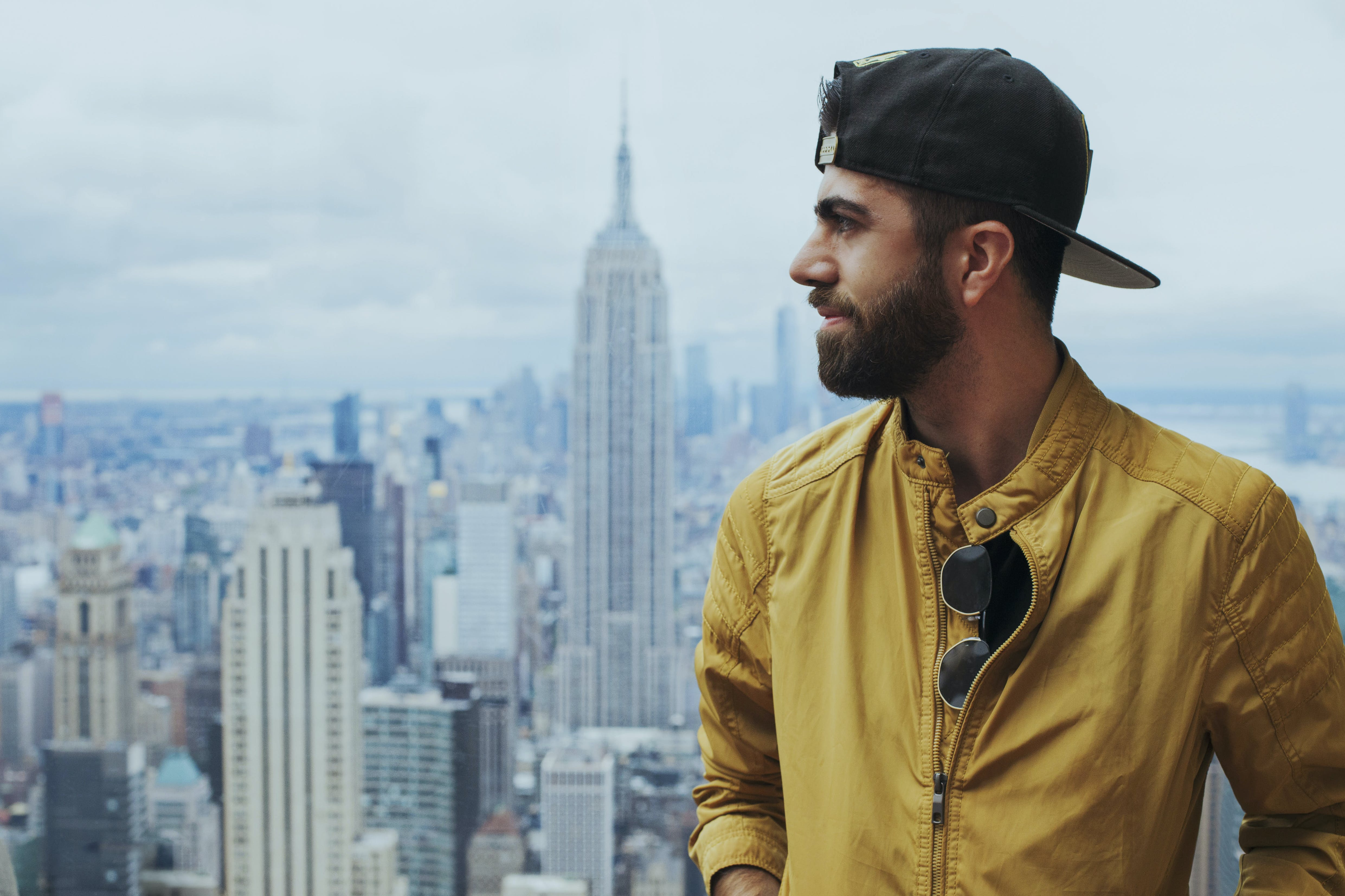 Portrait Photo of Man in Yellow Zip-up Jacket Near Empire State Building