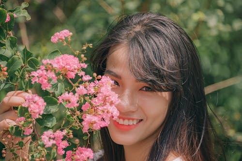 Photography of Smiling Woman Near Flowers
