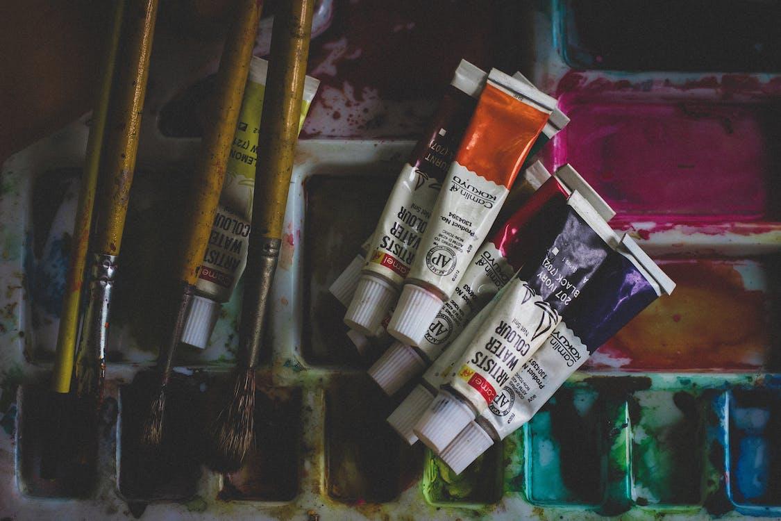 Photo of Acrylic Paint Soft-tubes Beside Paintbrushes