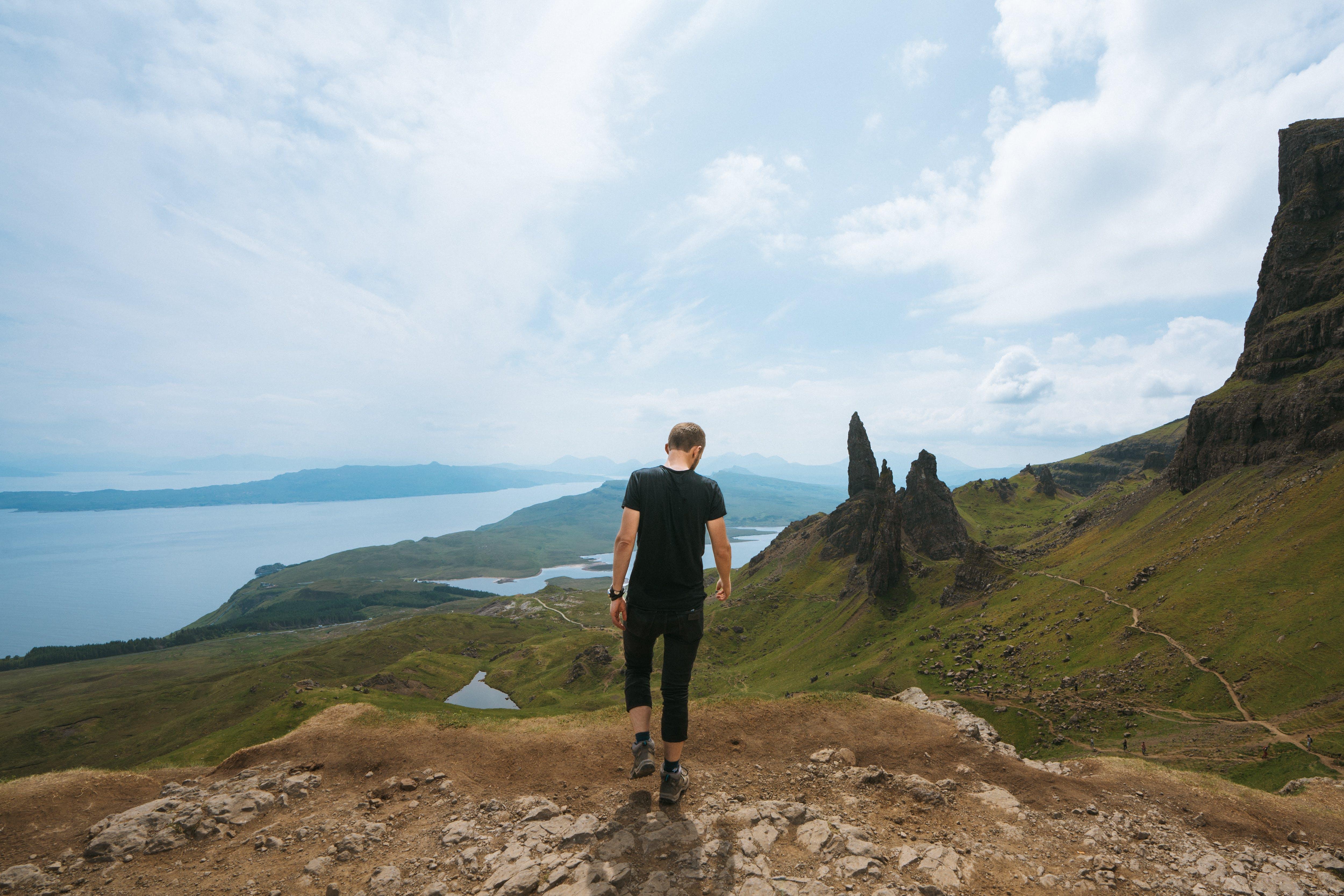 Man Wearing Black T-shirt Standing On Cliff