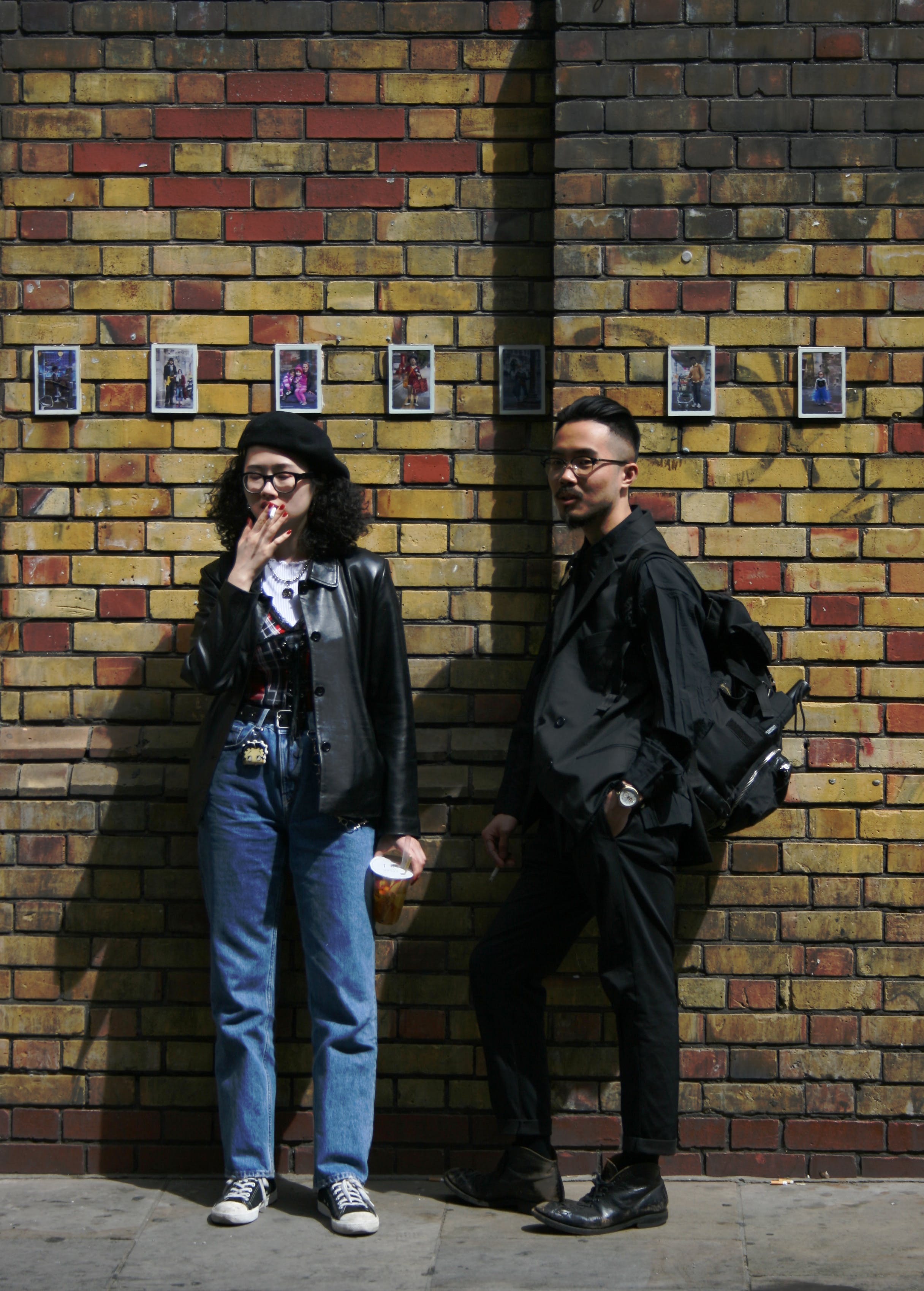 Man and Woman Standing in Front of Concrete Wall