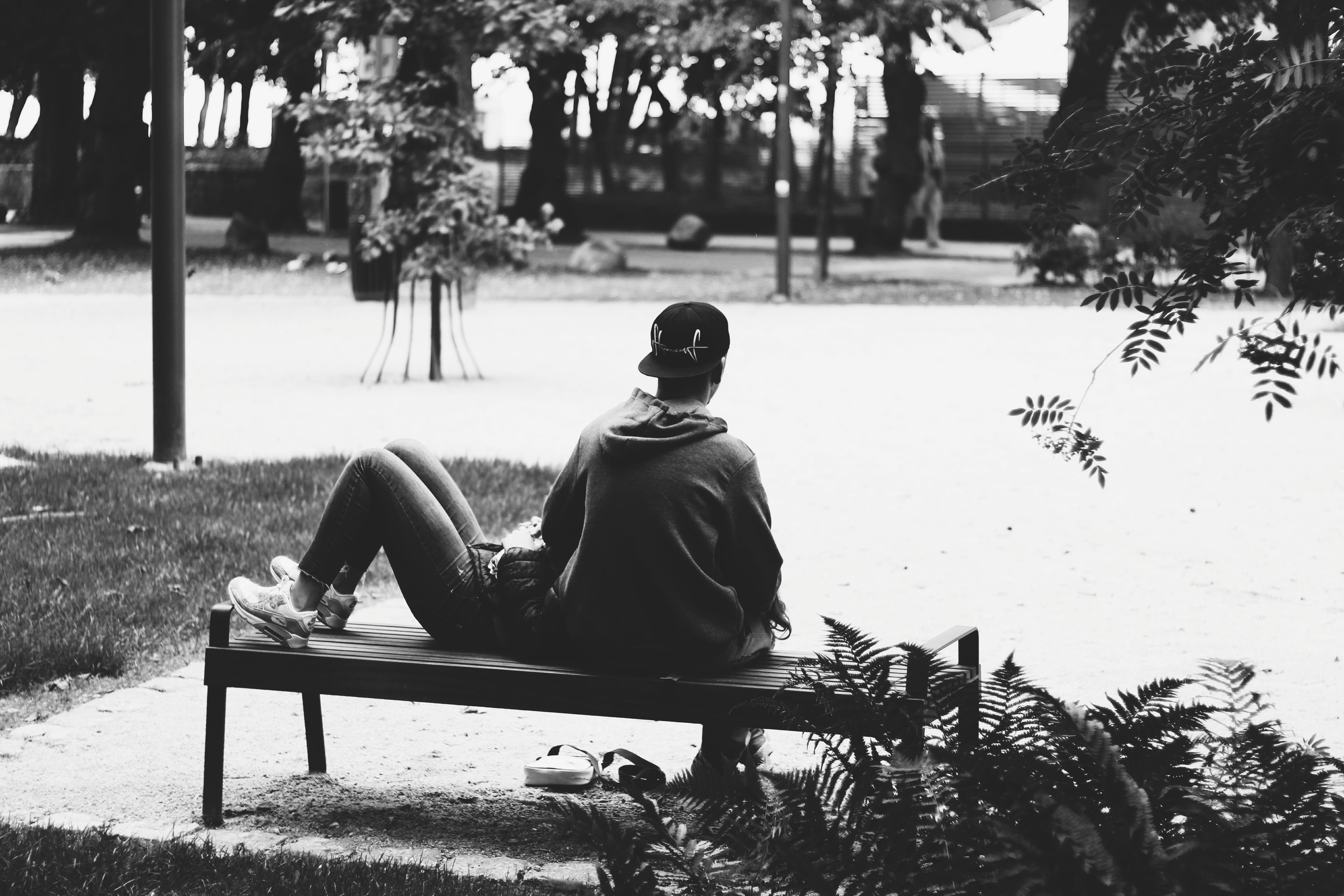 Grayscale Photo of a Couple sitting on a Bench